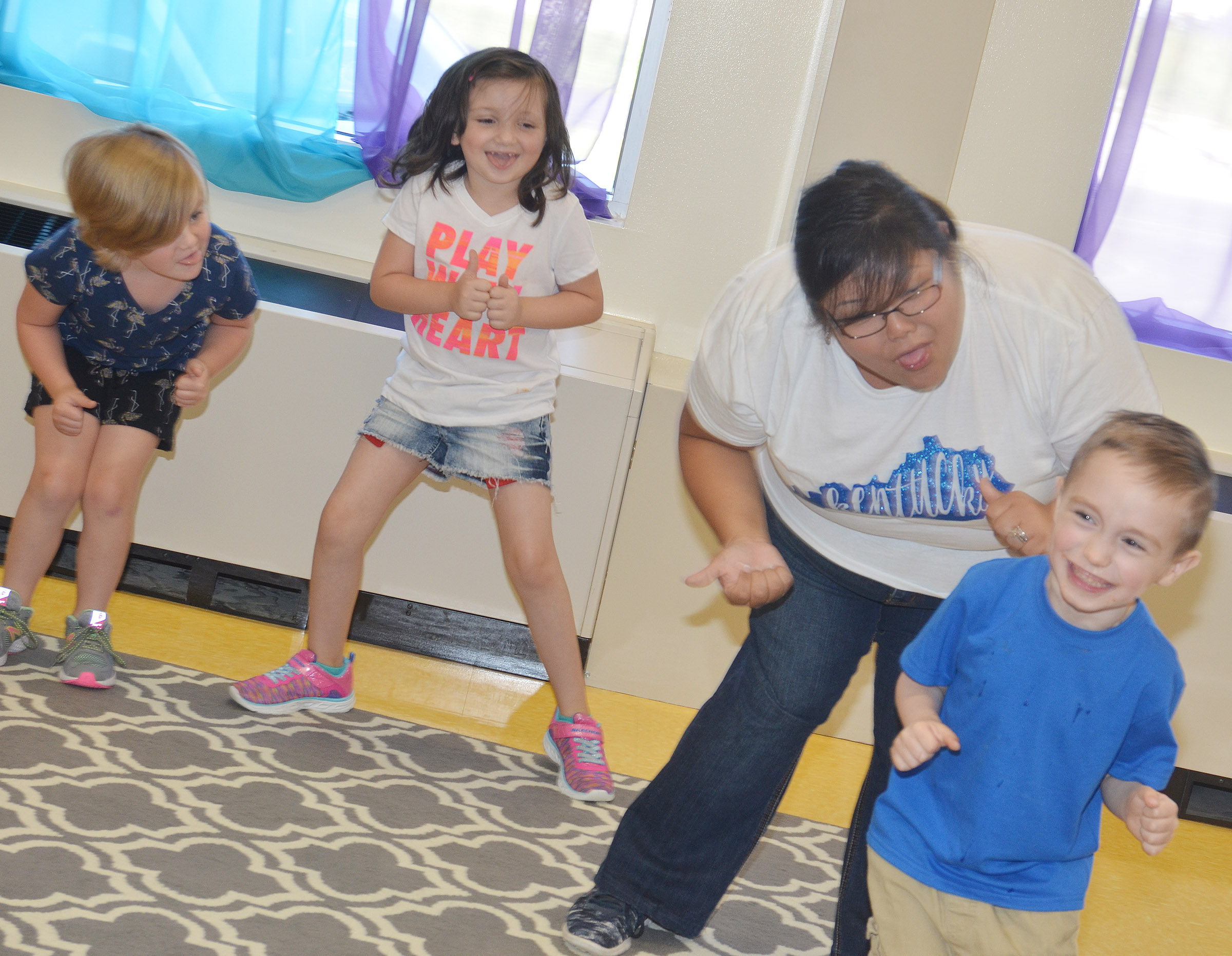 From left, CES kindergarteners Zoe Scharbrough, Abigail Smith and Joshua Dickens dance with instructional assistant Brittany Johnson.