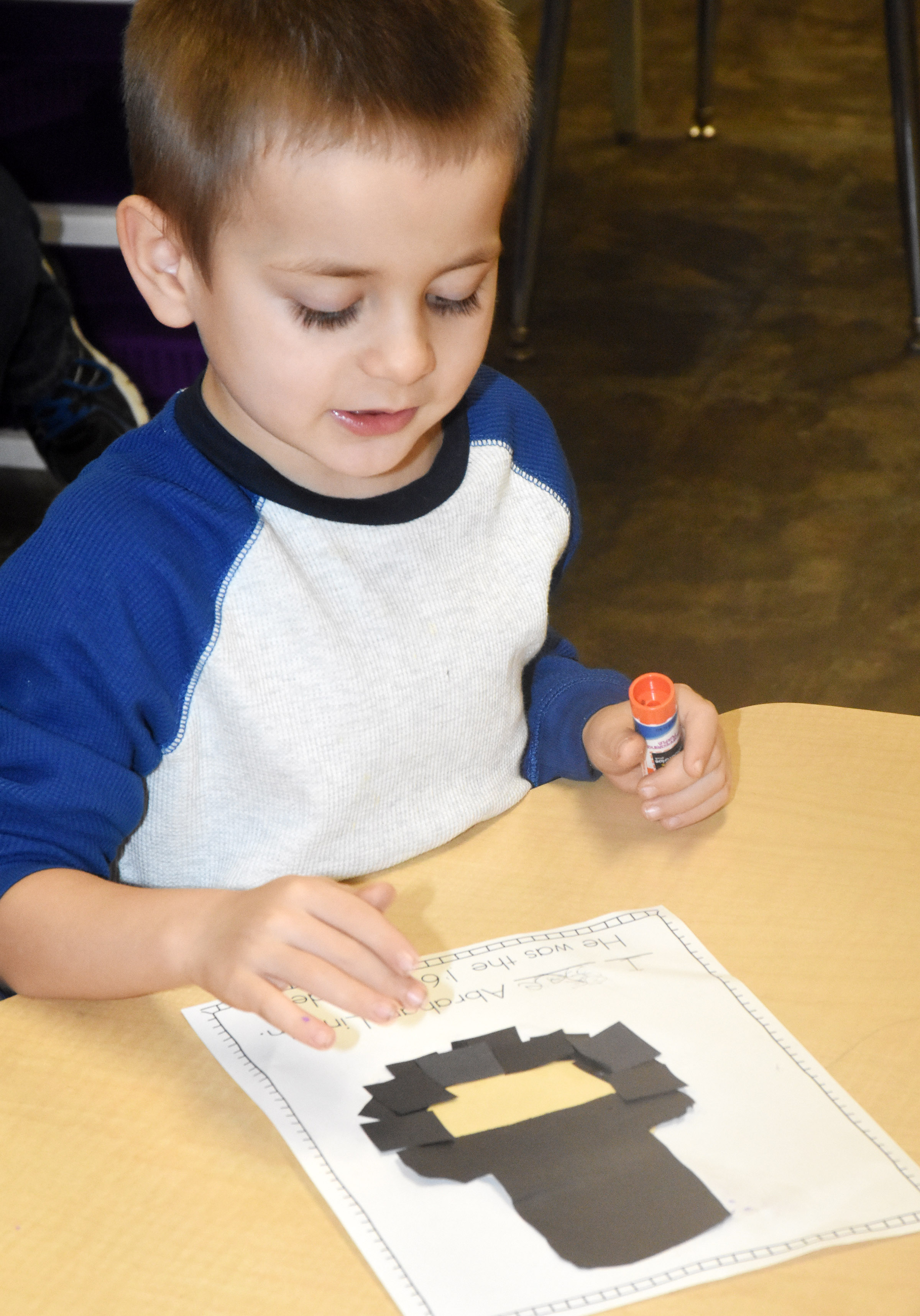 CES kindergartener Samuel Terry glues together construction paper as he makes his Abraham Lincoln.