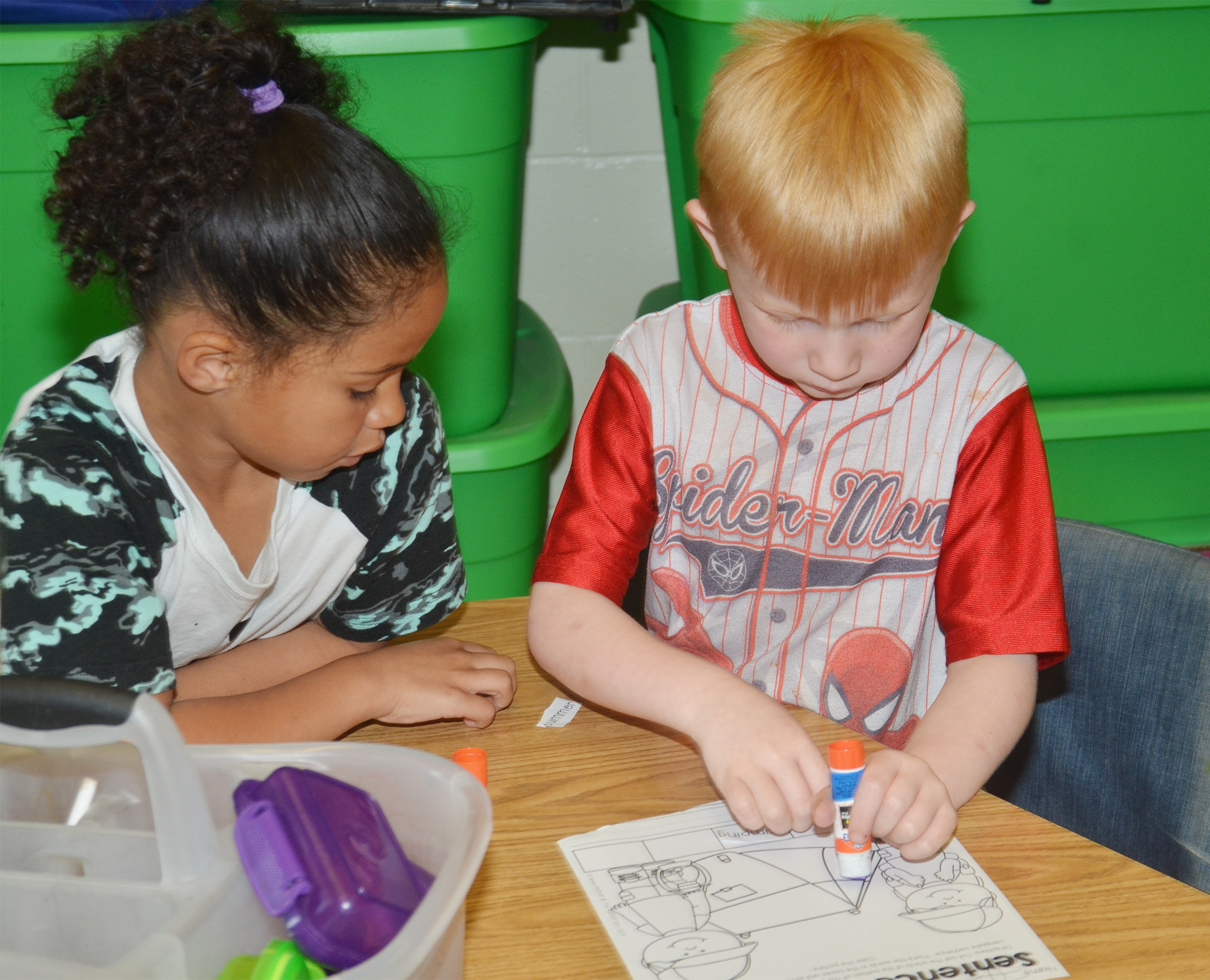 CES kindergarteners Jyra Welch, at left, and Jayden Maupin work together as they write a sentence about camping.