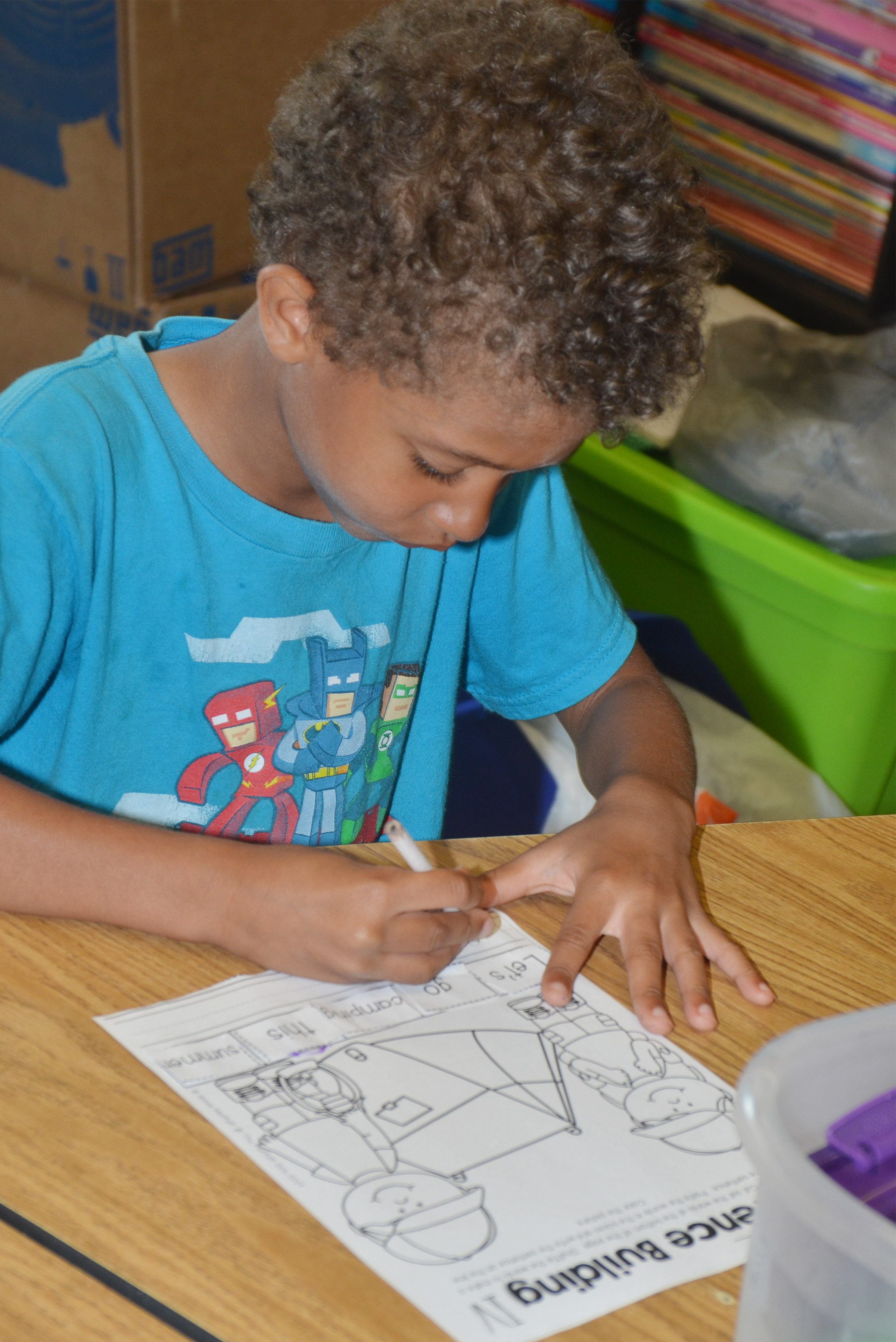 CES kindergartener Tyce Owens writes his sentence about camping.