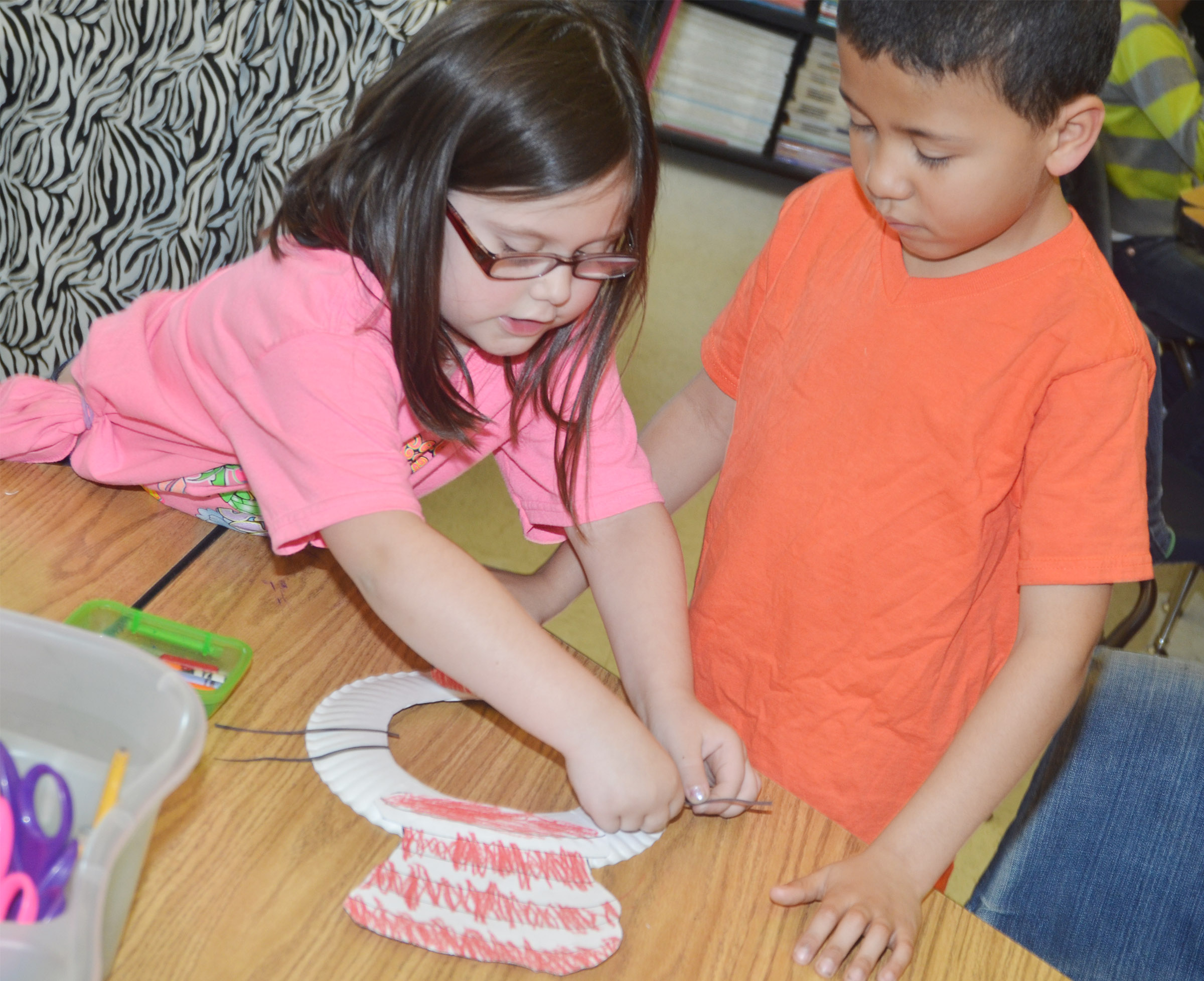 CES kindergartener Trinity Clark helps classmate Ahryan Wilson glue his whiskers to his mask.