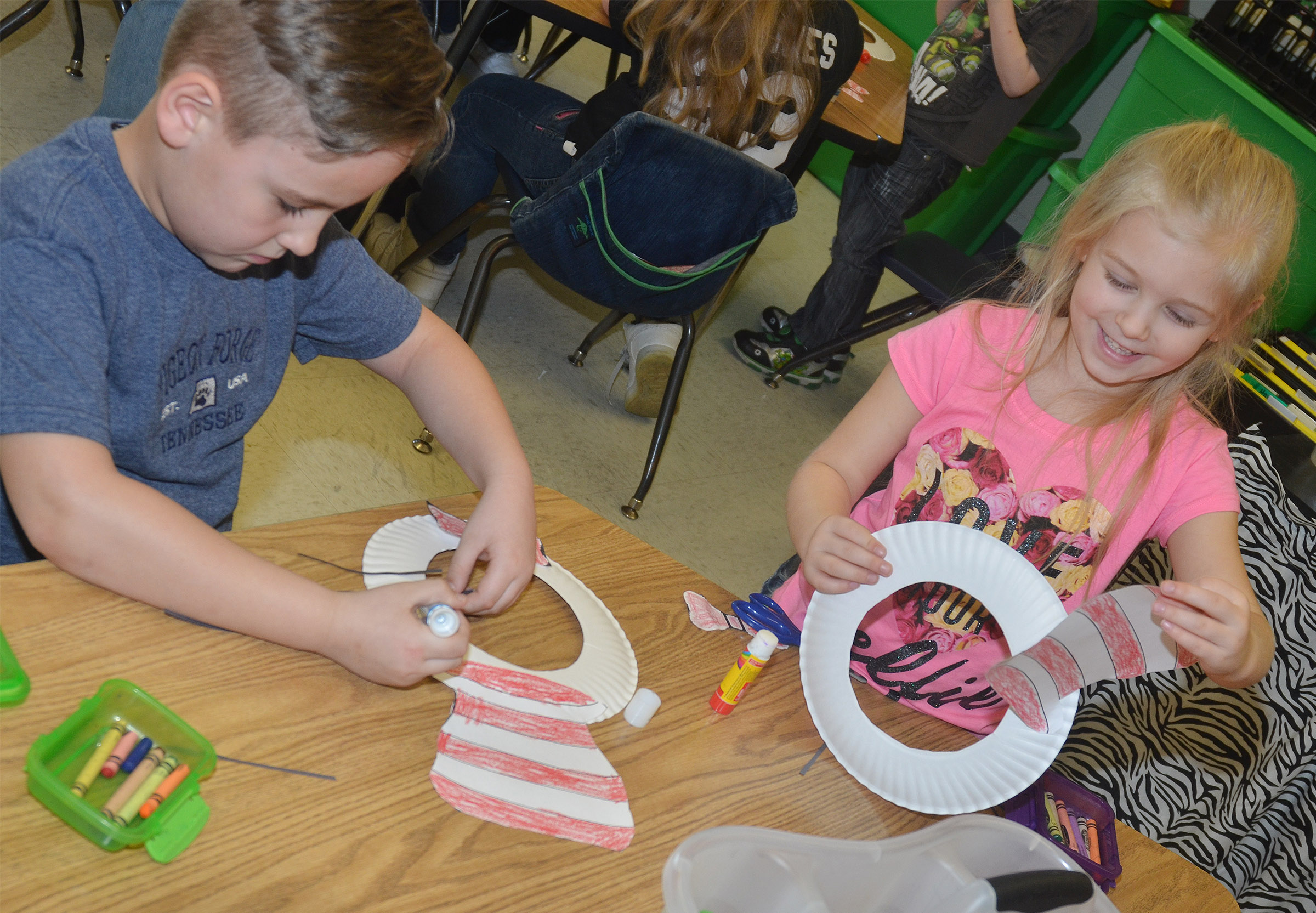 CES kindergarteners Braxton Rhodes, at left, and Aubrey Novak glue their Cat in the Hat hats to their paper plates.
