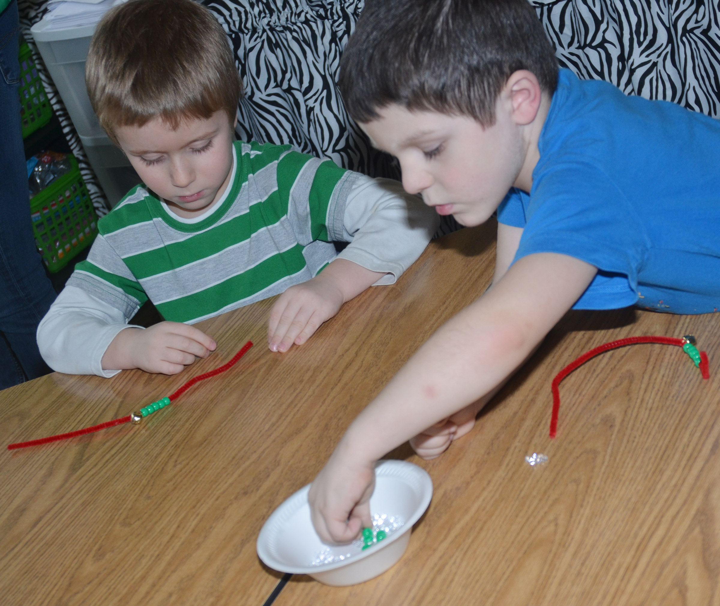 CES kindergarteners Alex Newcomb, at left, and Michael Priddy make jingle bell bracelets.