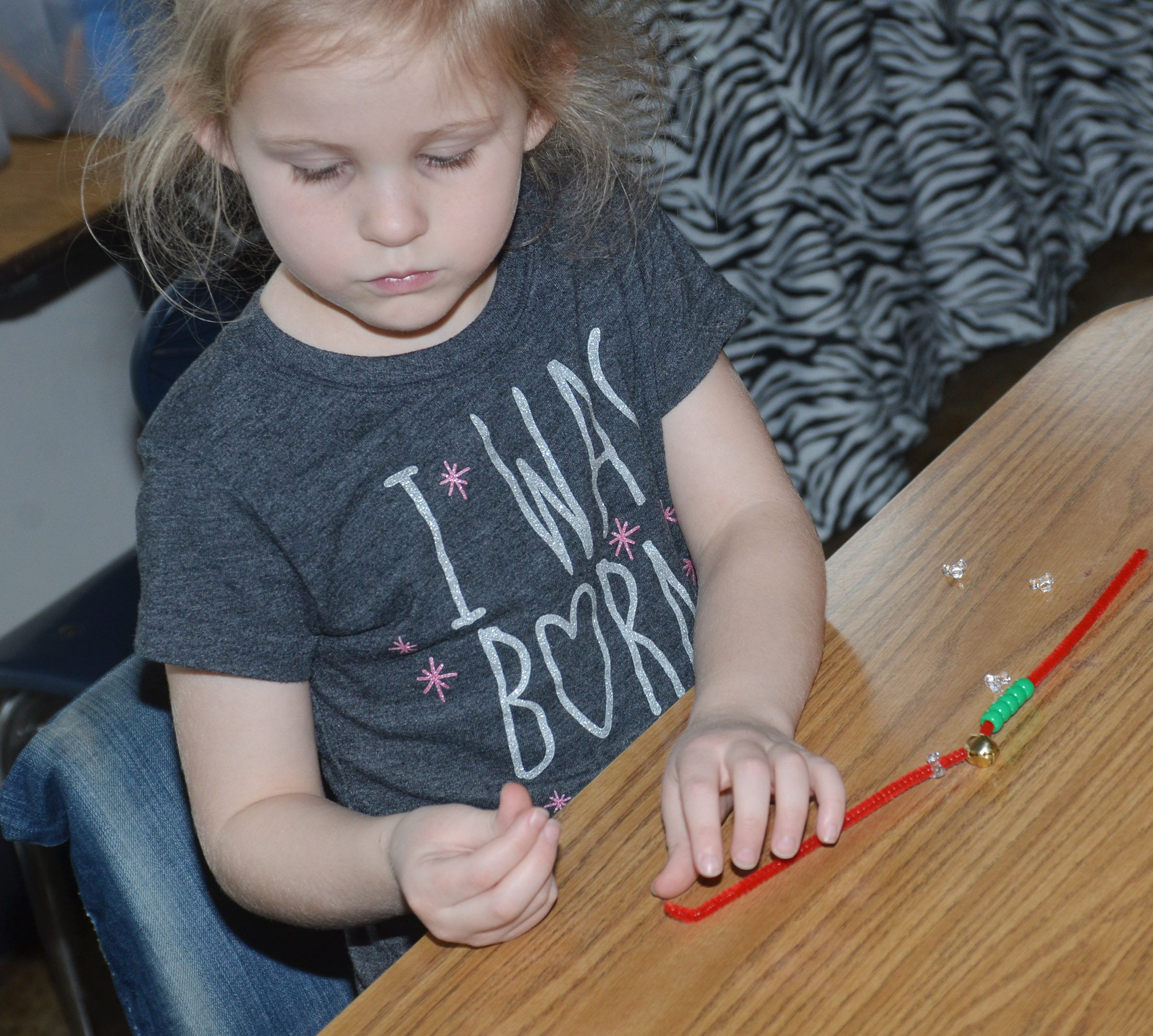 CES kindergartener Riley Bright makes a jingle bell bracelet.