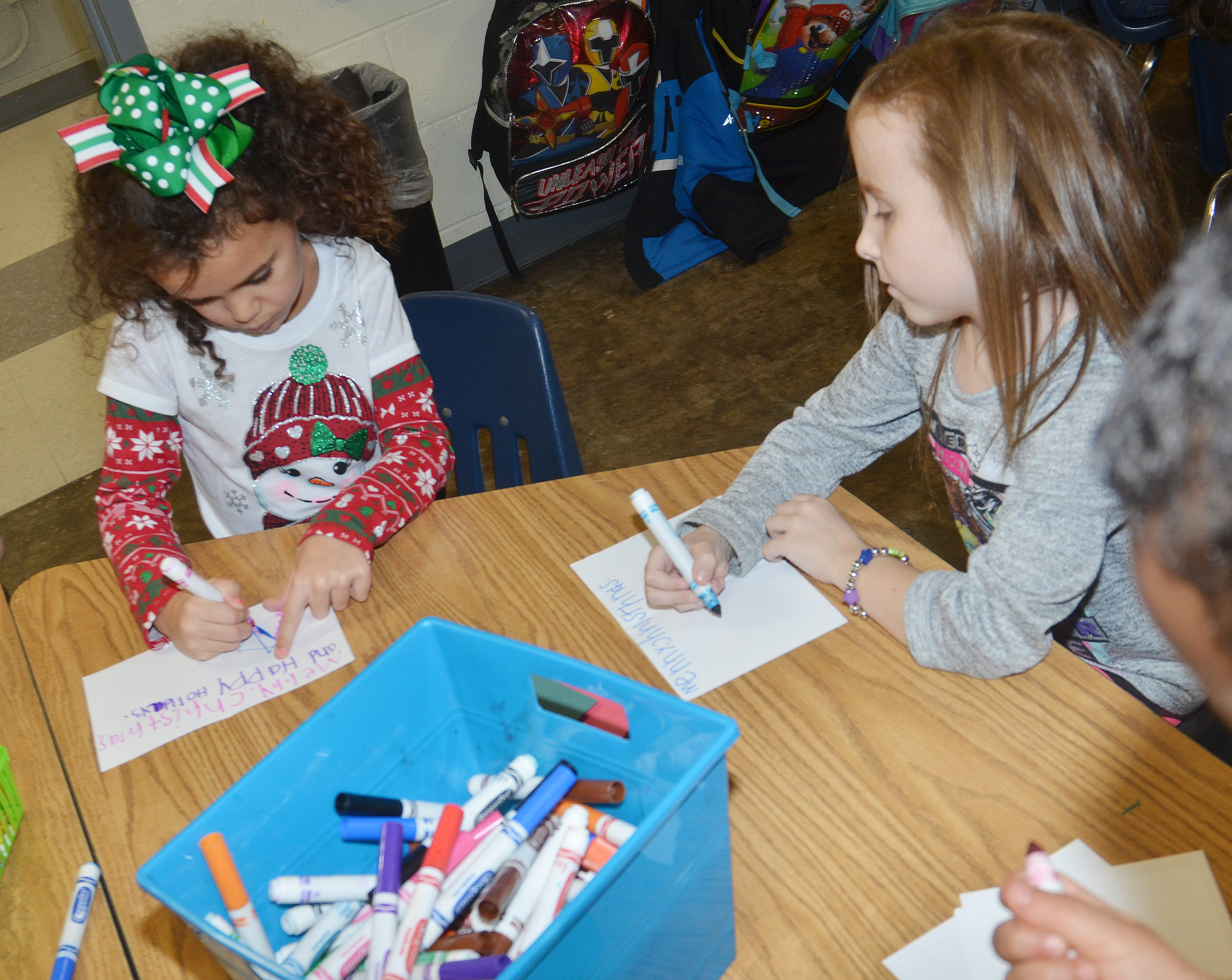 CES kindergarteners Adelyn Litsey, at left, and Tabitha Leggett make Christmas cards.