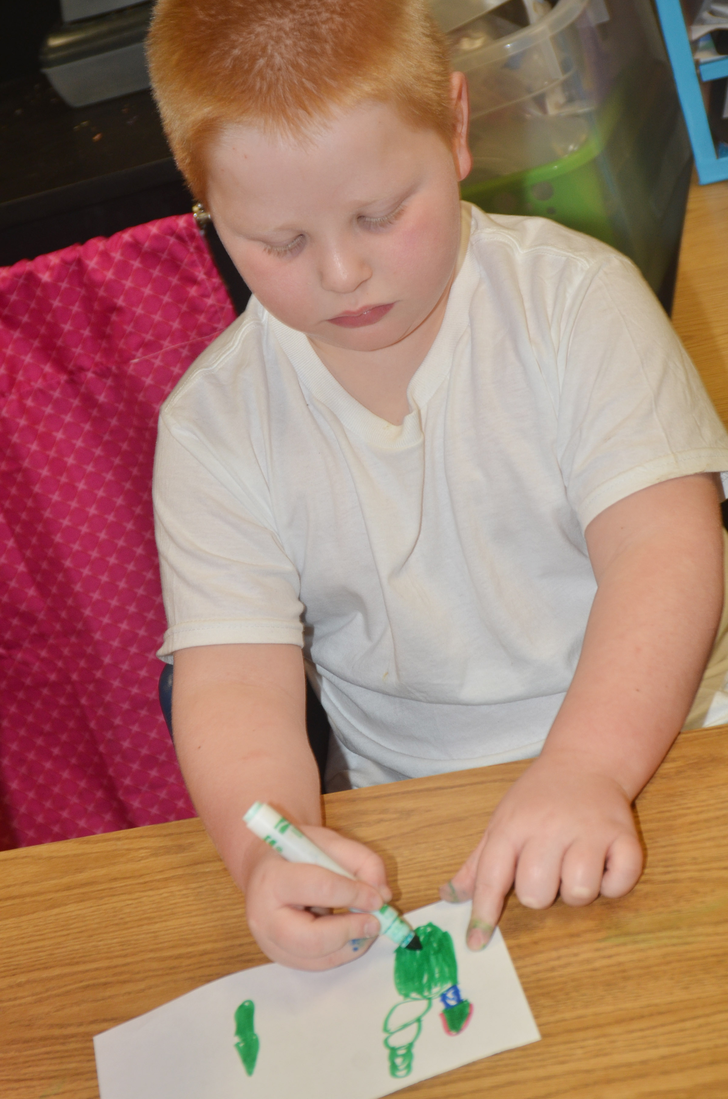 CES kindergartener Konnar Hicks makes a Christmas card.