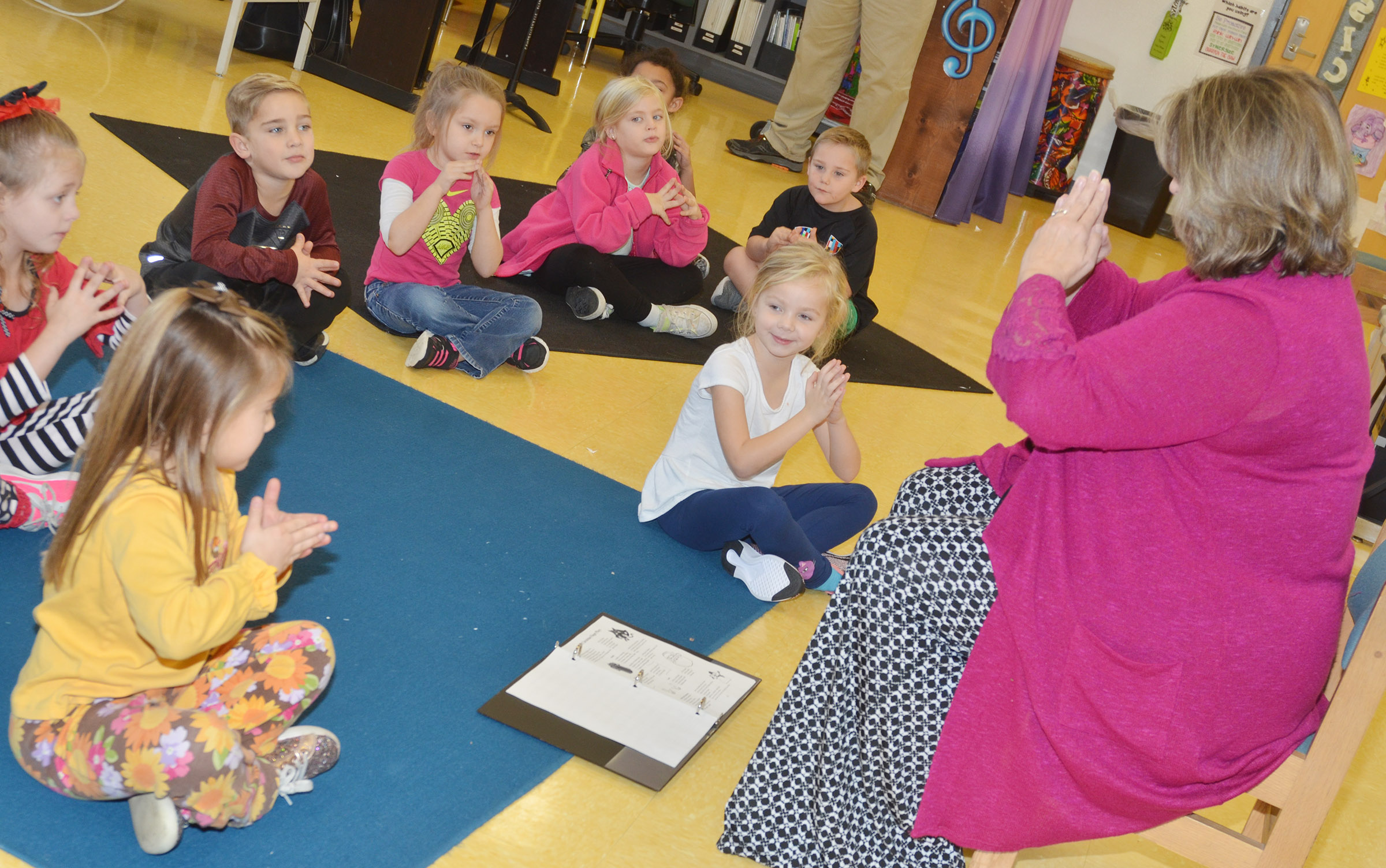 CES music teacher Cyndi Chadwick leads kindergarteners as they sing a Christmas song.