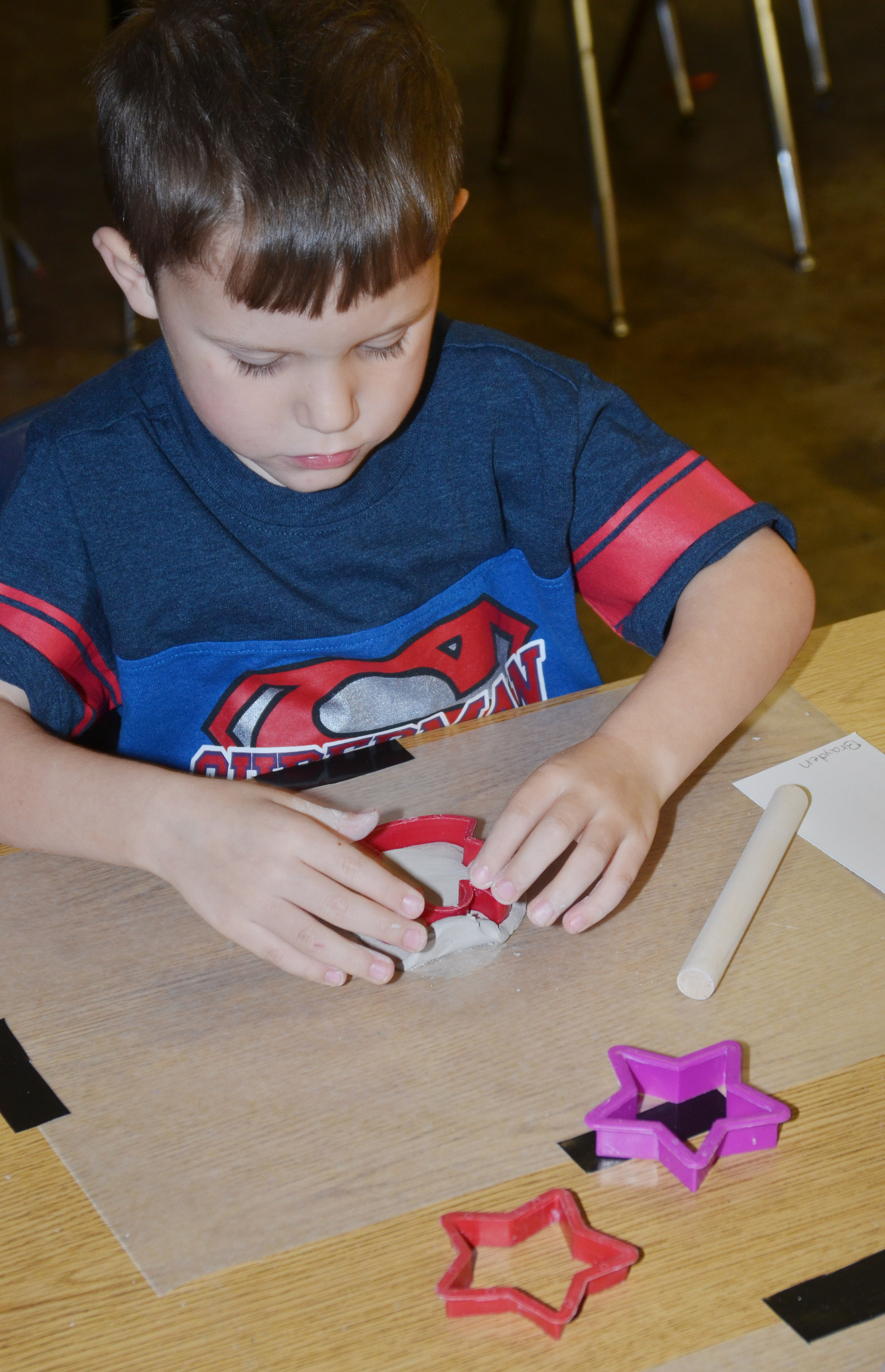 CES kindergartener Brayden Carmicle uses a cookie cutter to shape his ornament.