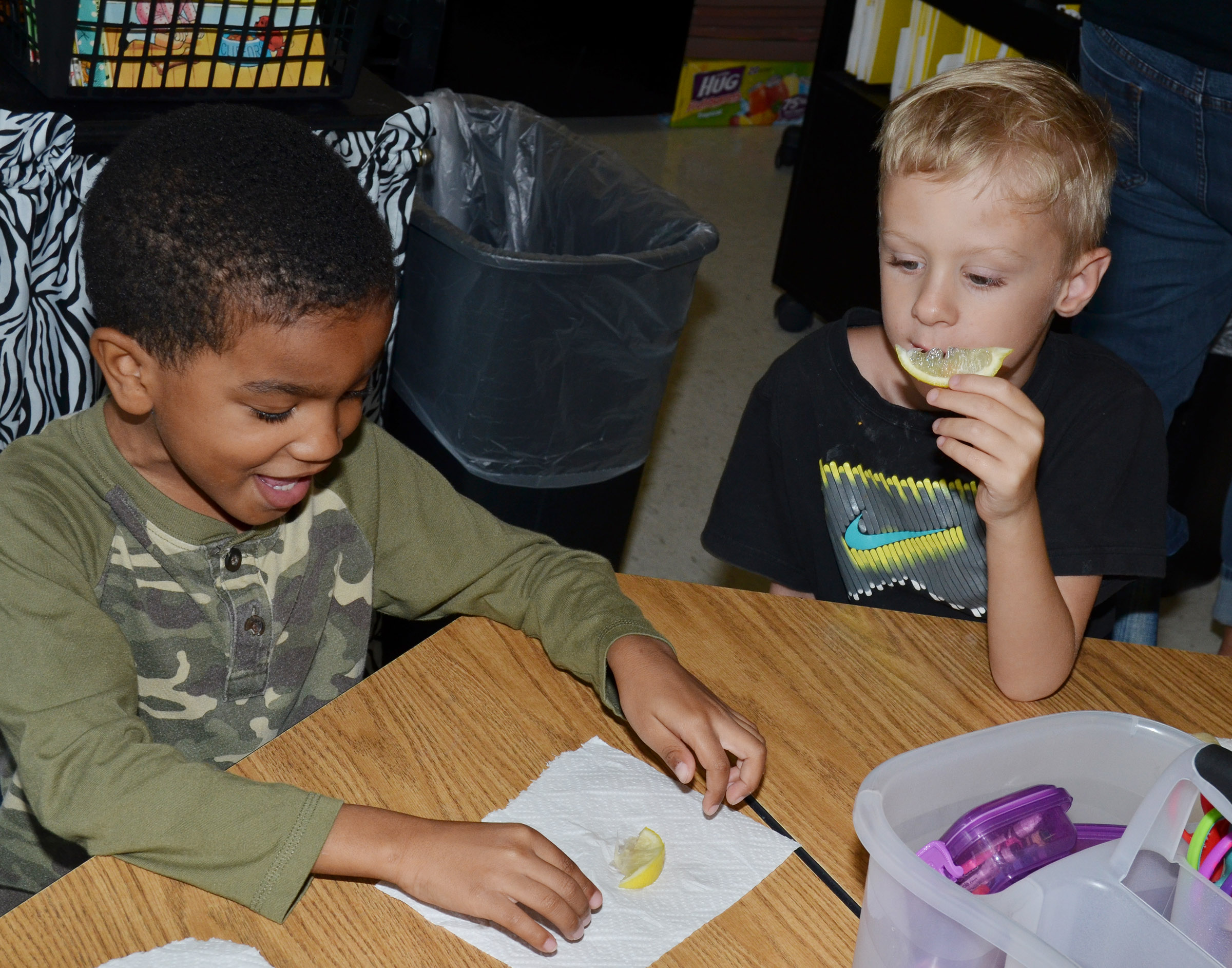 CES kindergarteners Donavon Bell, at left, and Lukas Adams sample lemons.