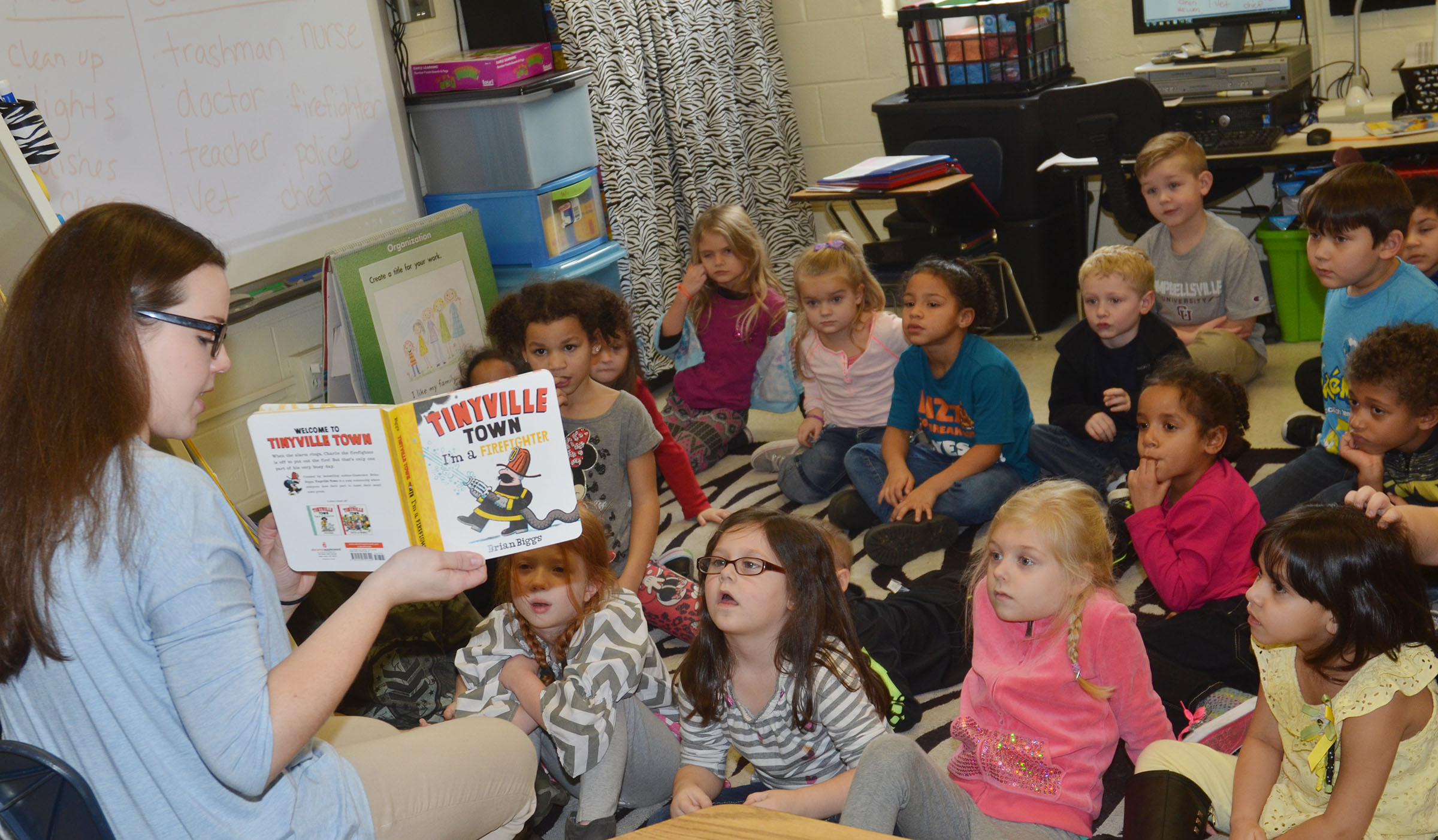 CES kindergarten student teacher Amanda Hamilton reads to Lisa Wiseman's students about how a firefighter is a community helper.