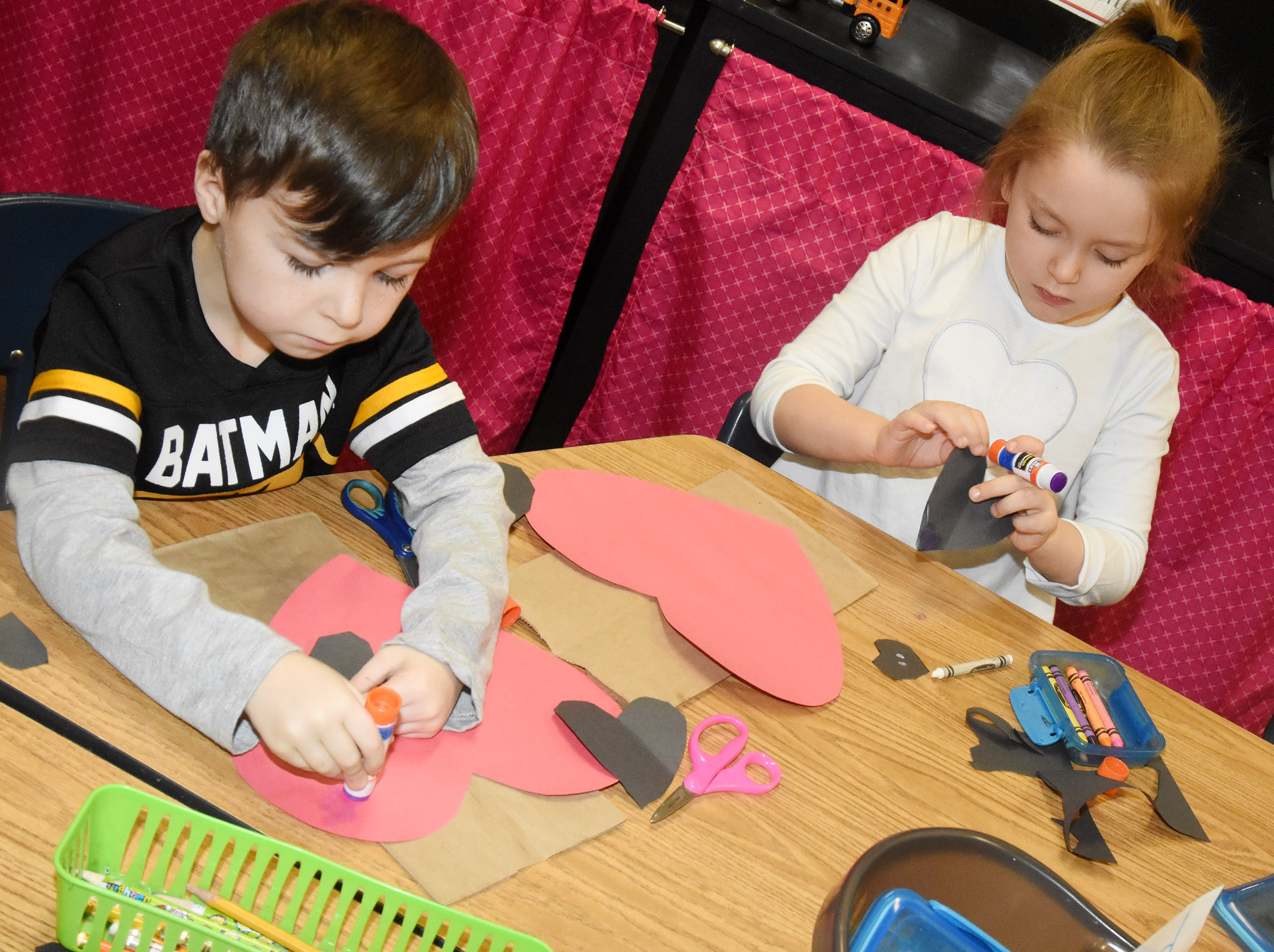 CES kindergarteners Bentley Wilhoite, at left, and Myah Learmond glue together their puppy dog Valentine bags.