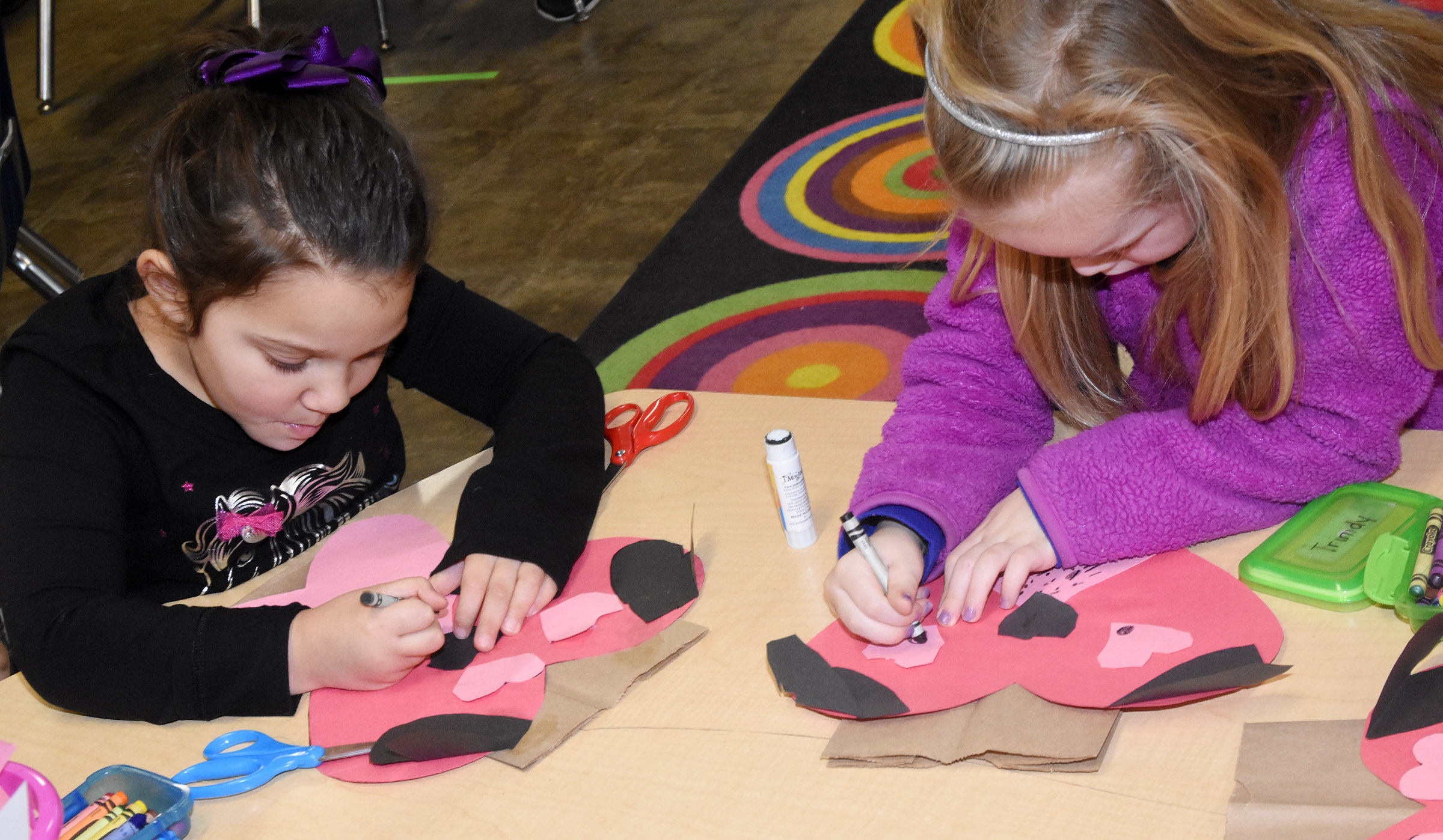 CES kindergarteners Addisyn Taylor, at left, and Trinidy Gribbins add eyes and whiskers to their puppy dog Valentine bags.