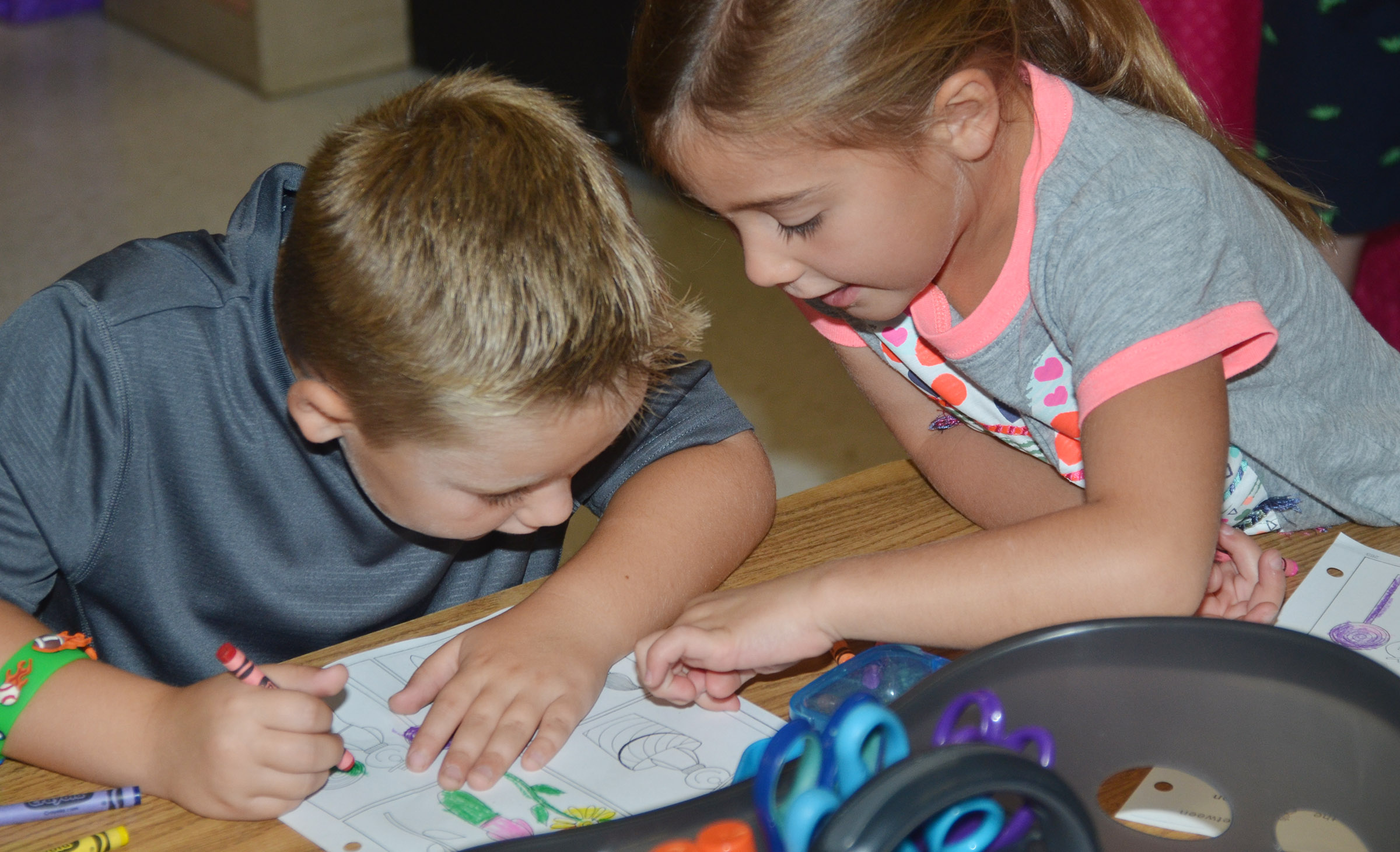 CES kindergarteners Jacob Sandidge, at left, and Blakely Gray talk as they finish their worksheets.
