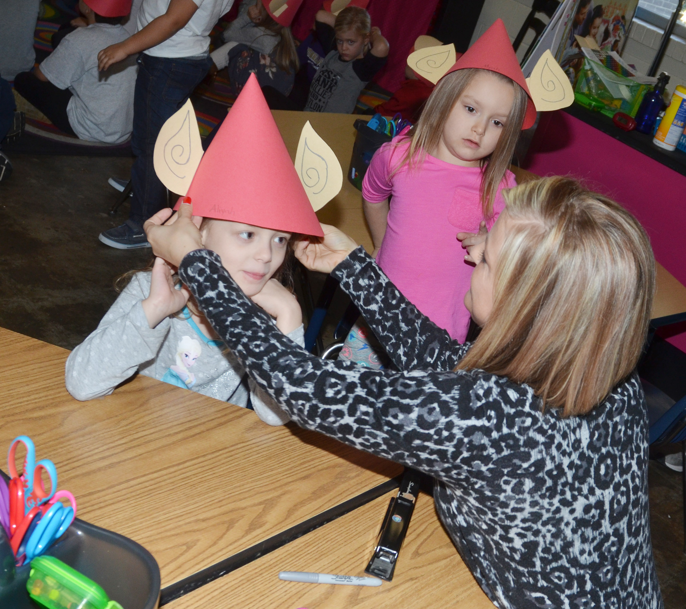 CES kindergarten teacher Leanna Cundiff helps Aliyah Garrett try on her elf hat.