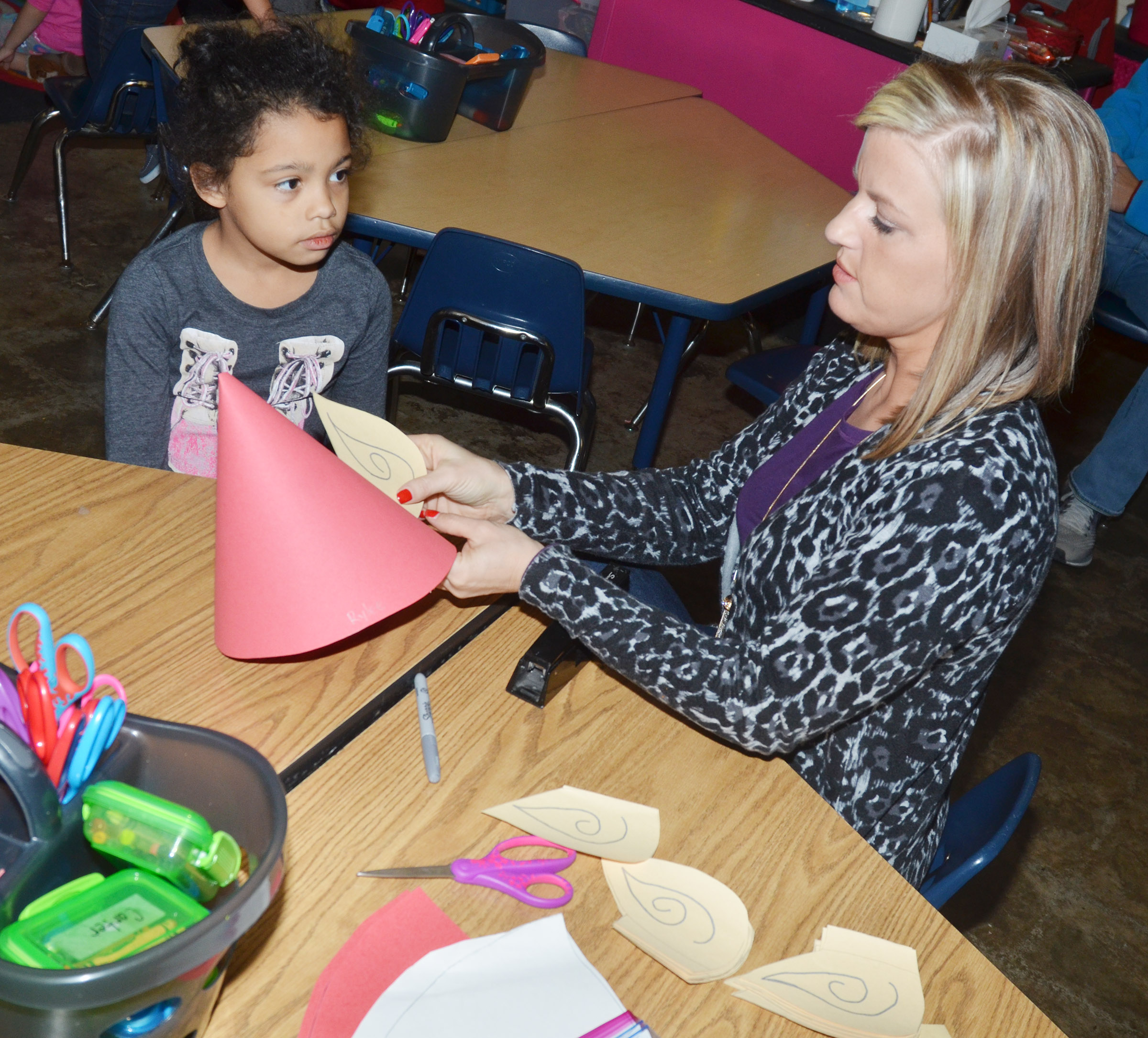 CES kindergarten teacher Leanna Cundiff helps Rylee Karr make her elf hat.