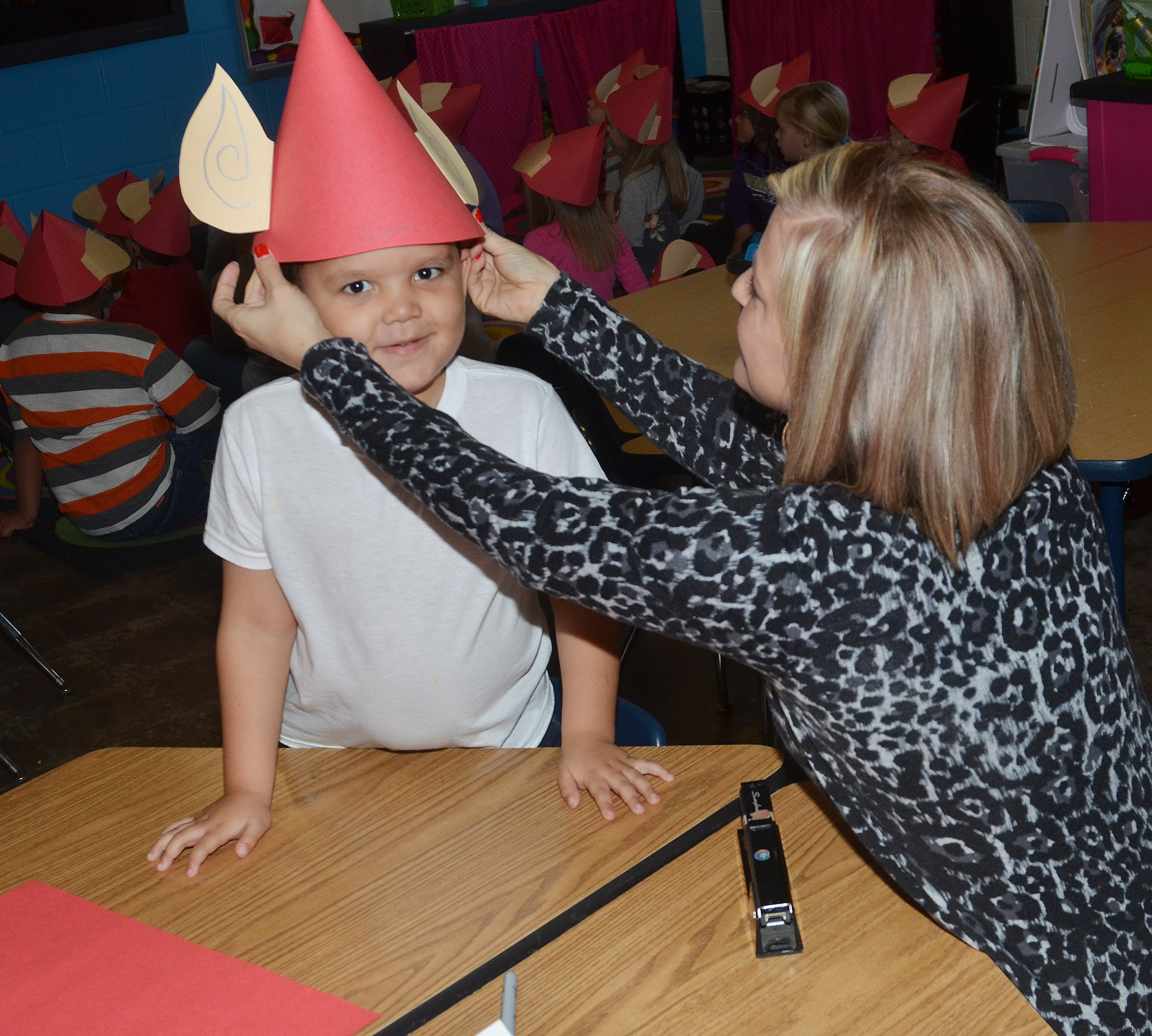 CES kindergarten teacher Leanna Cundiff helps Kingson Duncan try on his elf hat.