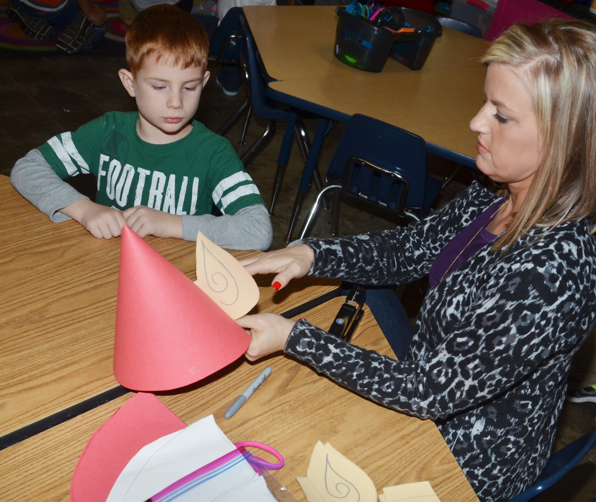 CES kindergarten teacher Leanna Cundiff helps Kennon Dotson make his elf hat.