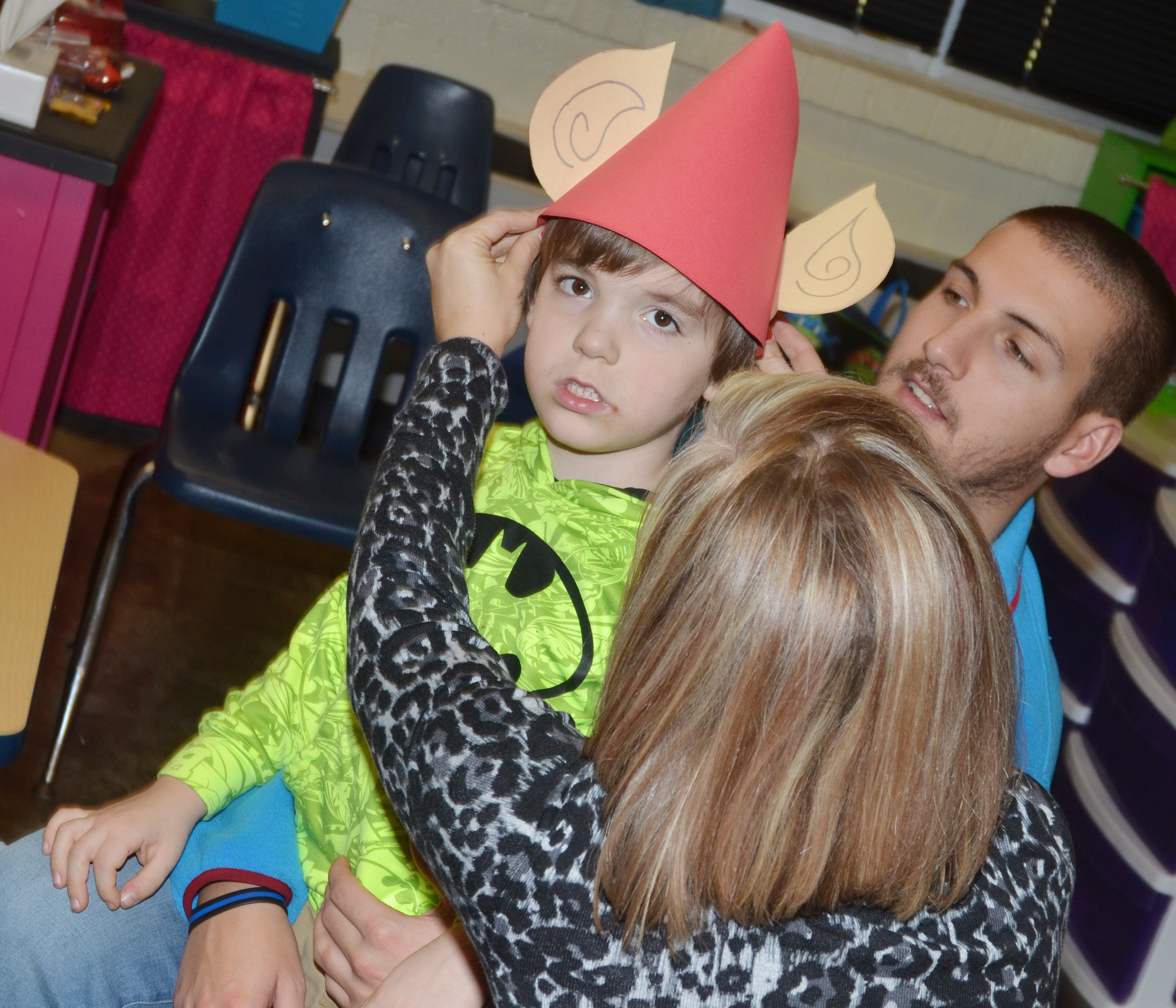 CES kindergarten teacher Leanna Cundiff and instructional assistant Zach Durham help Finley Williams try on his elf hat.