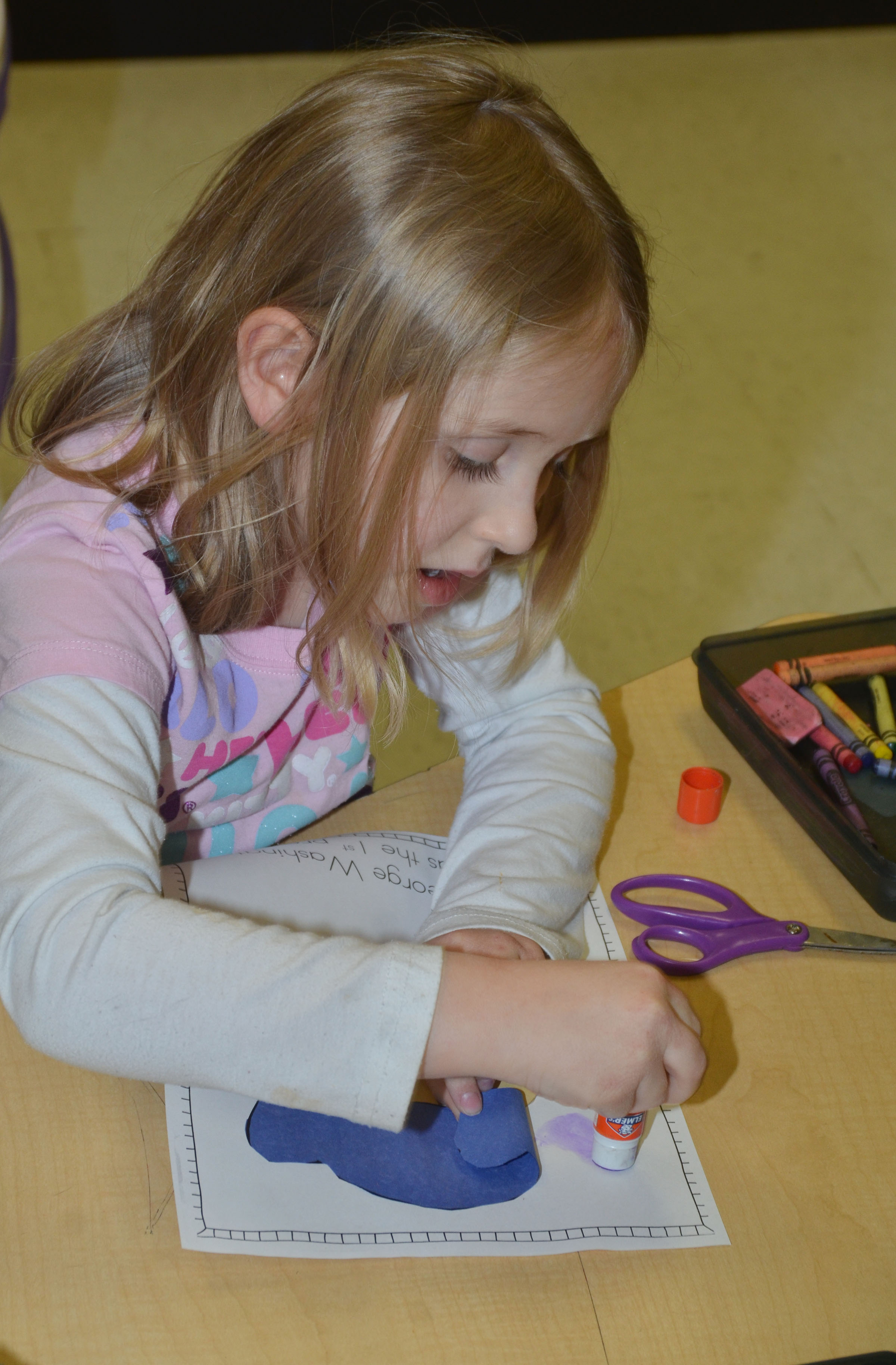 CES kindergartener LeeAnna Garvin glues together her George Washington figure.