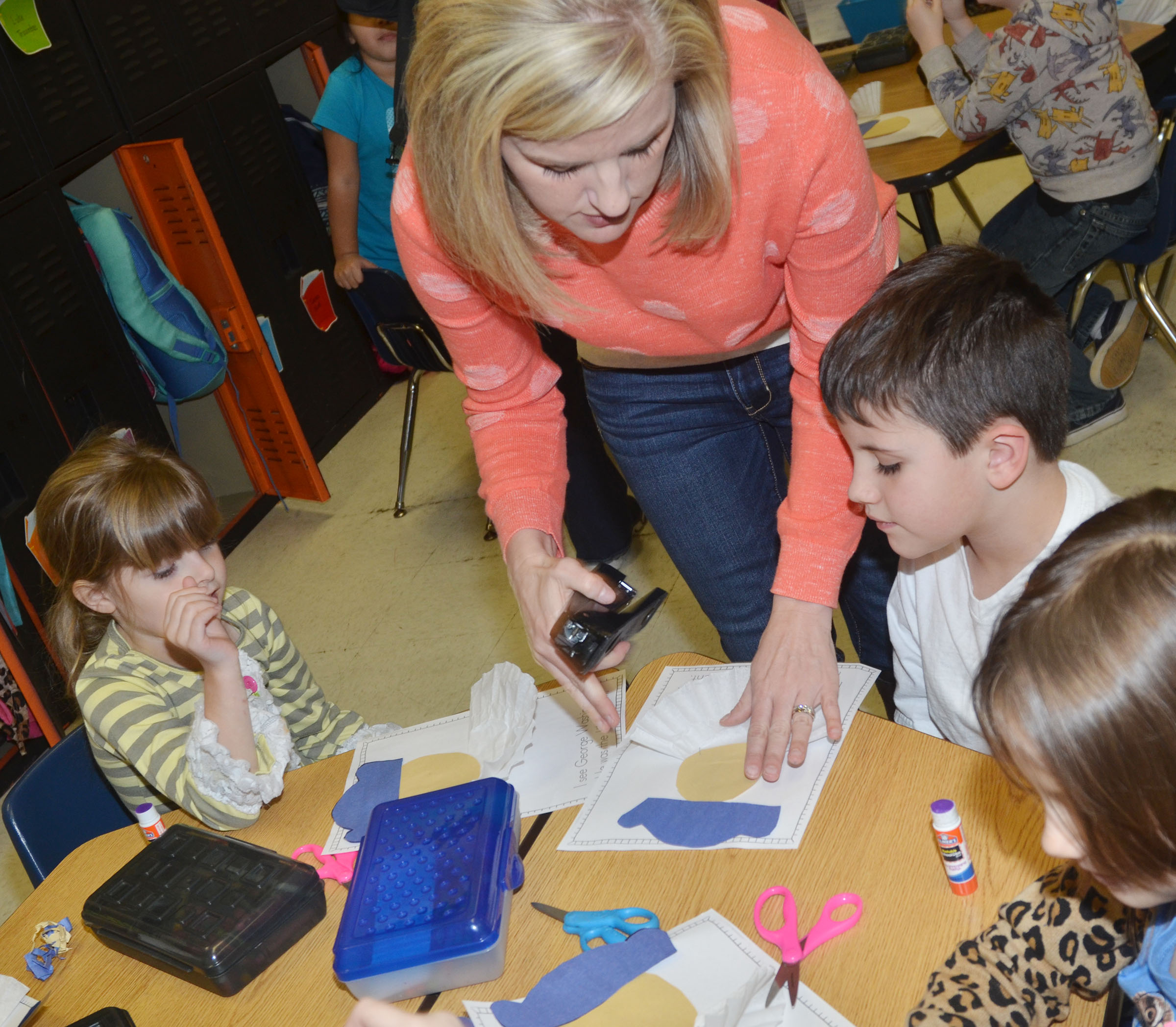 CES kindergarten teacher Leanna Cundiff helps Madison Wilhoite, at left, and Casen Meredith make their George Washington figures.