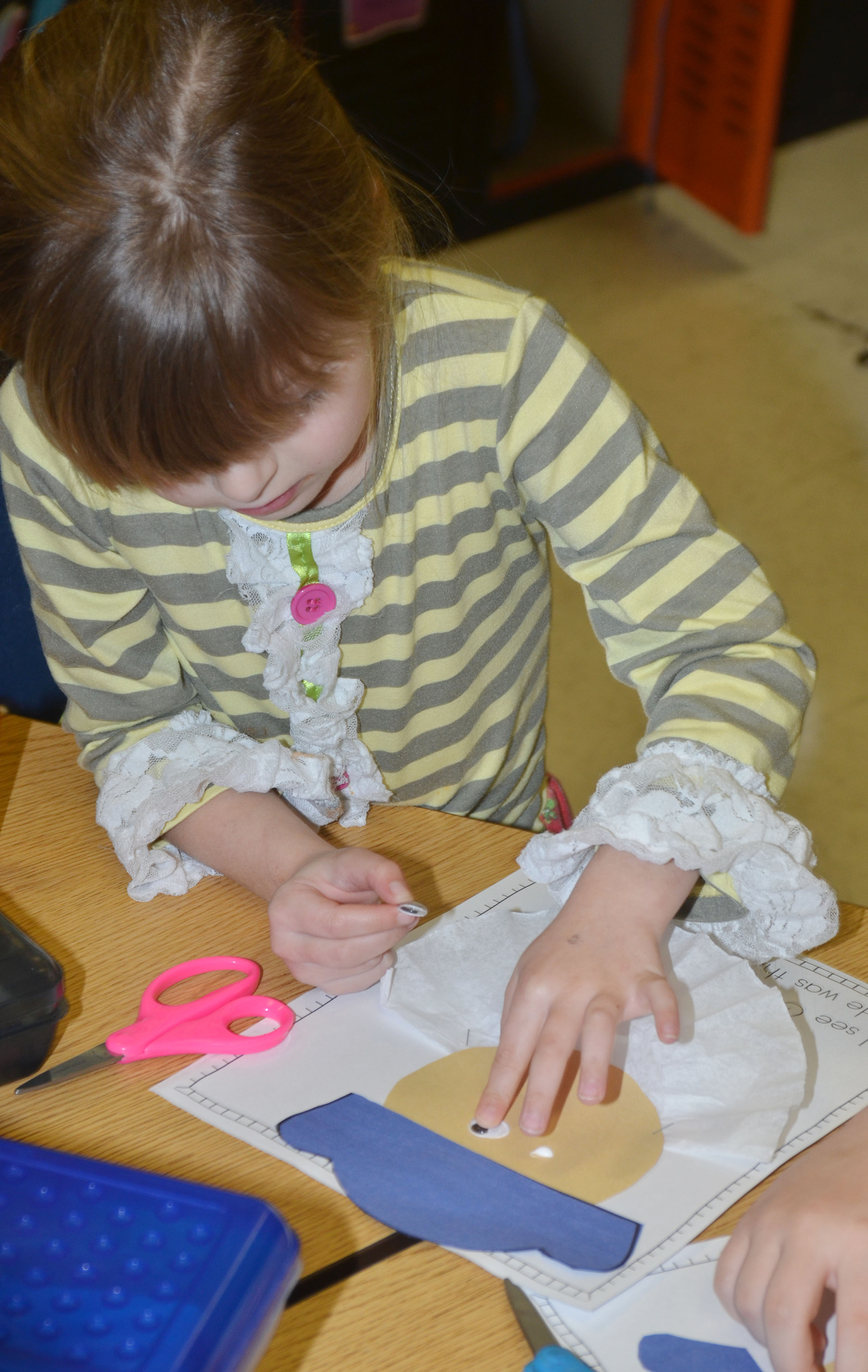 CES kindergartener Madison Wilhoite glues eyes on her George Washington figure.