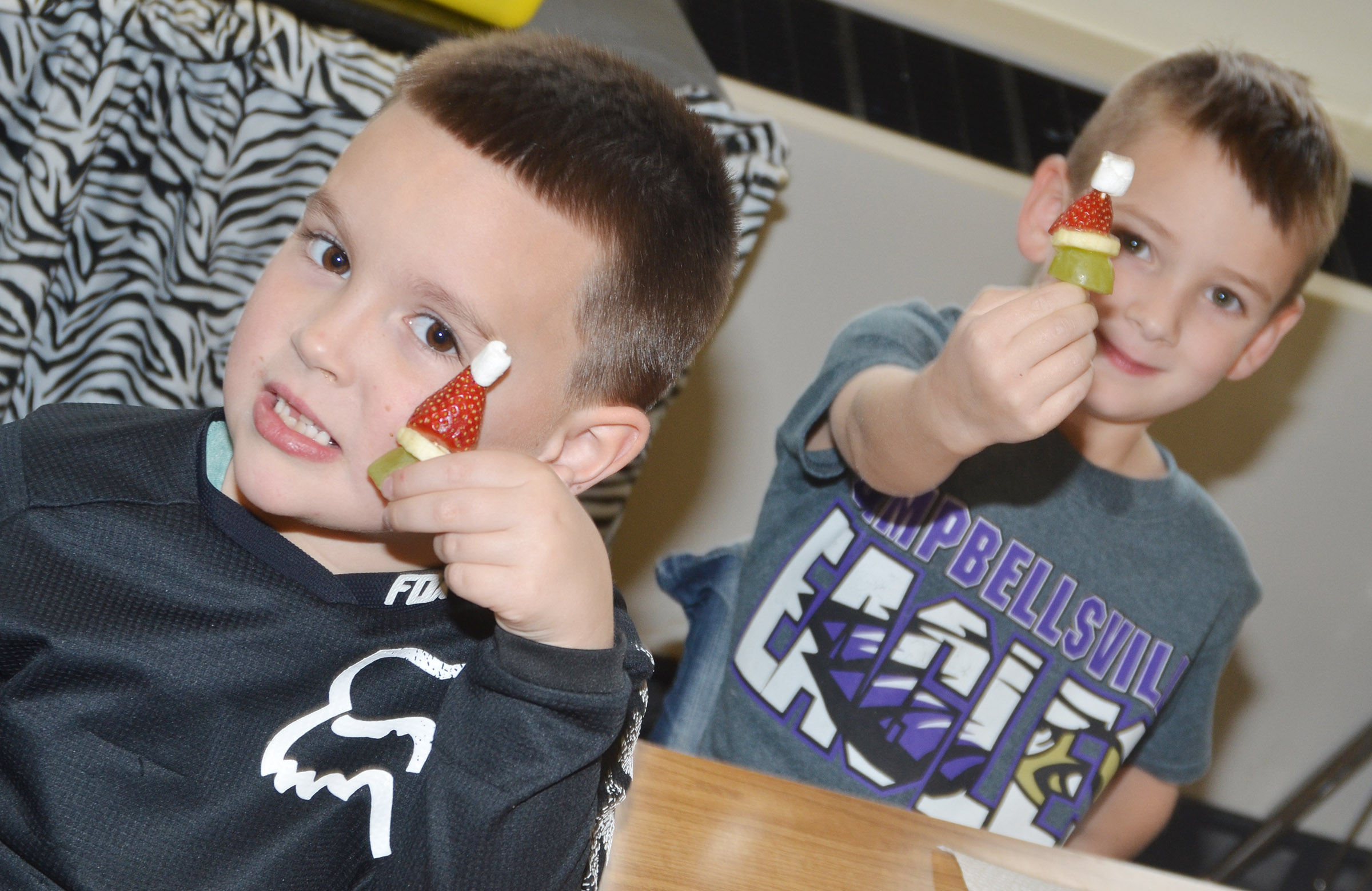CES kindergarteners Dawson Morton, at left, and Cash Davis hold their Grinch snacks.