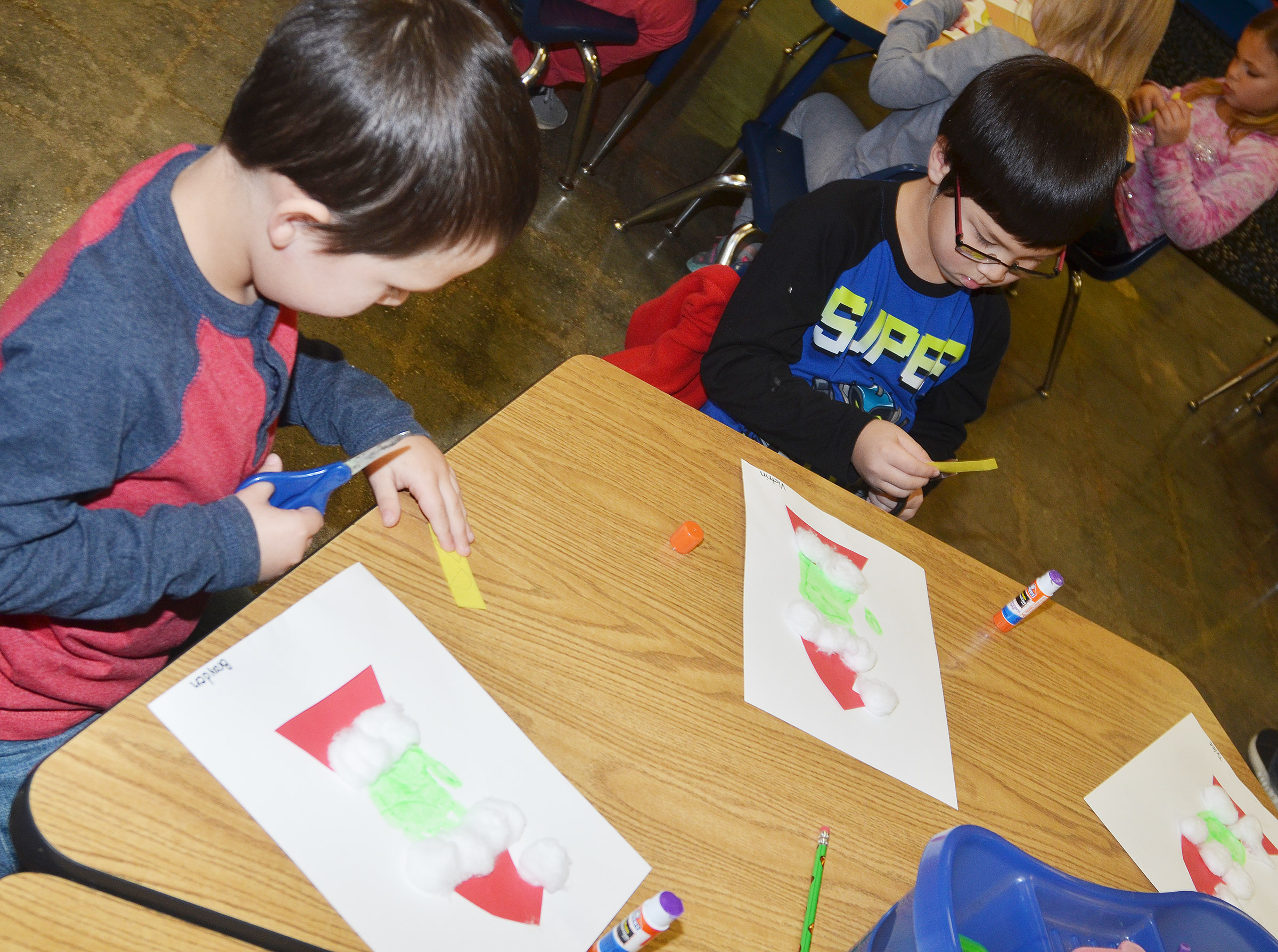 CES kindergarteners Brayden Perkins, at left, and Victrin Ramsey make their Grinch handprints.