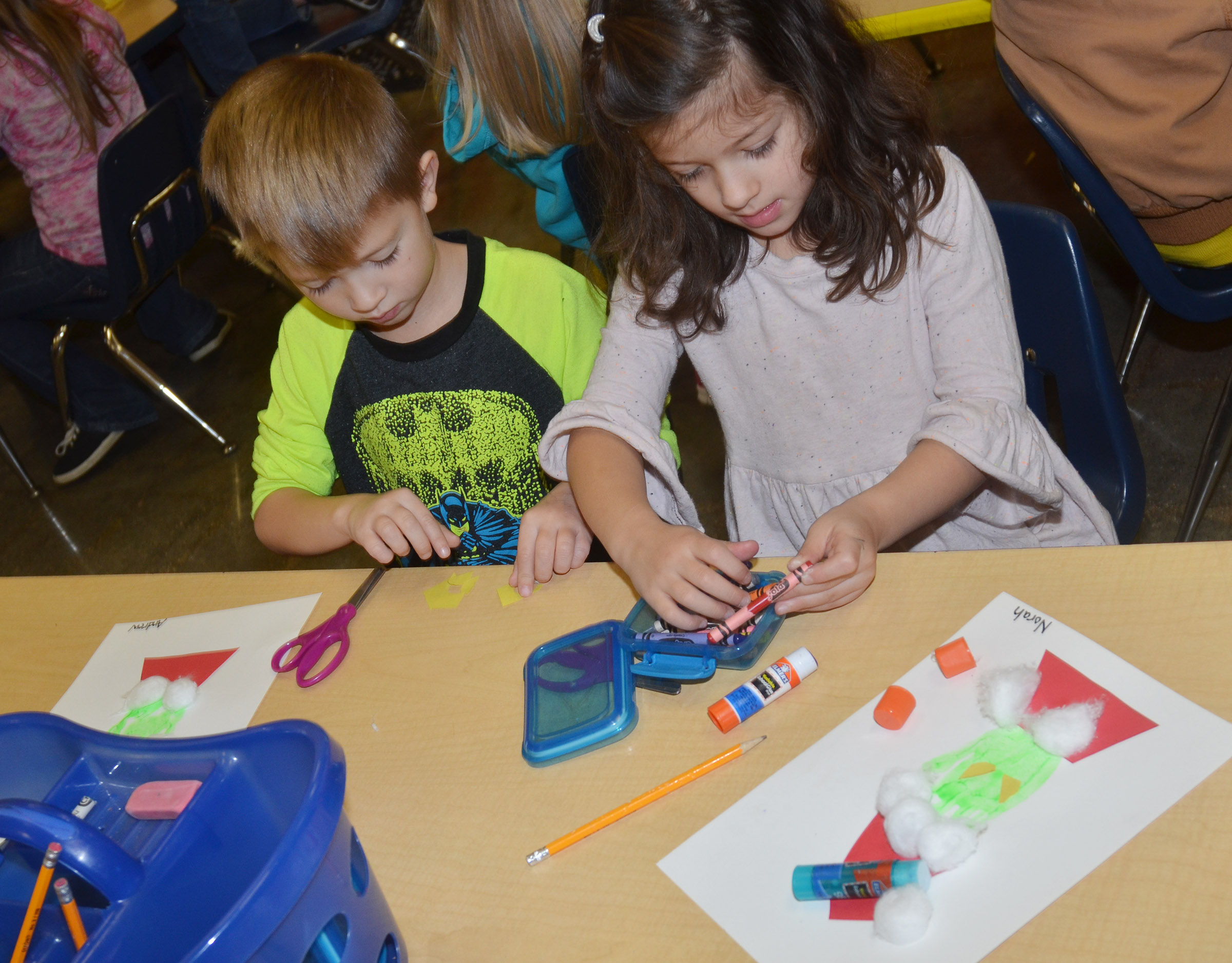 CES kindergarteners Andrew Stout, at left, and Norah Adkins make their Grinch handprints.