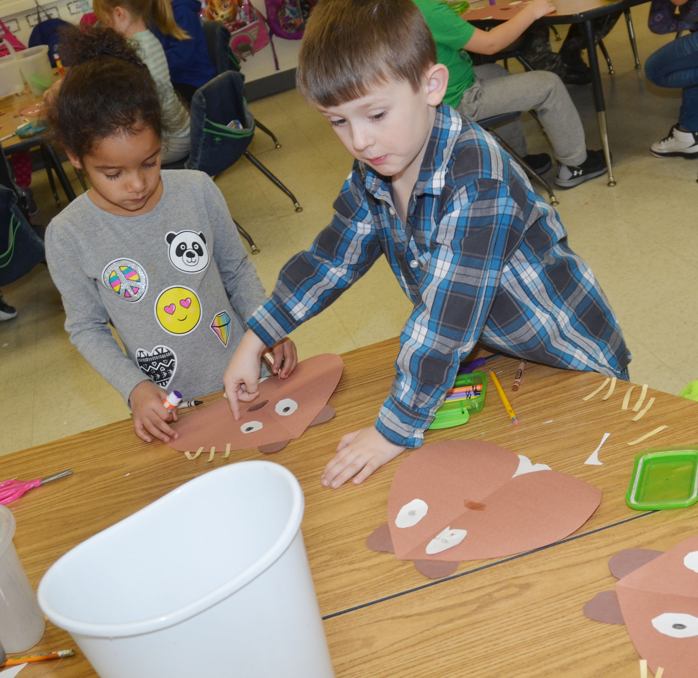 CES kindergarteners Kylei Thompson, at left, and Conor Gayheart glue their groundhogs together.