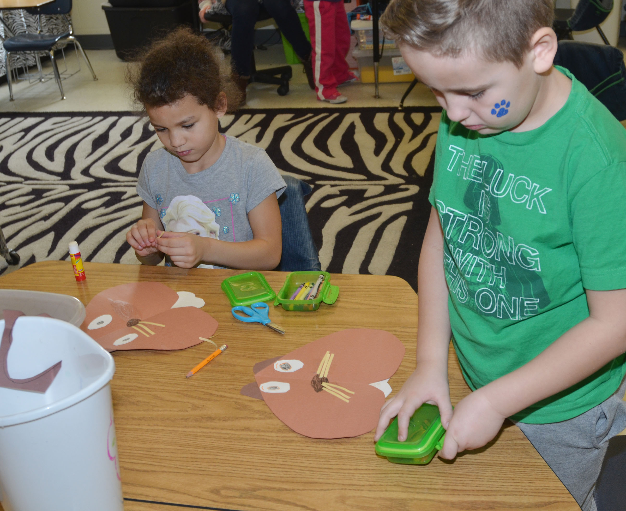 CES kindergarteners Aleeya Spaulding, at left, and Braxton Rhodes glue their groundhogs together.