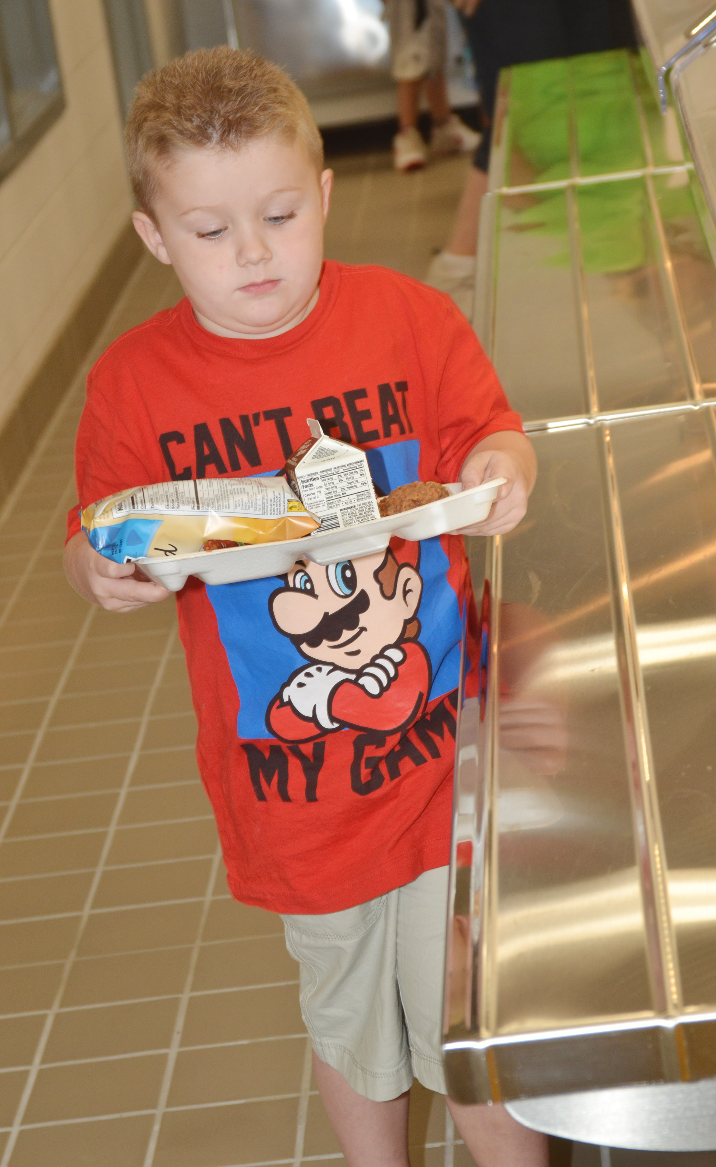 CES kindergartener Levi Dye carefully carries his lunch tray.