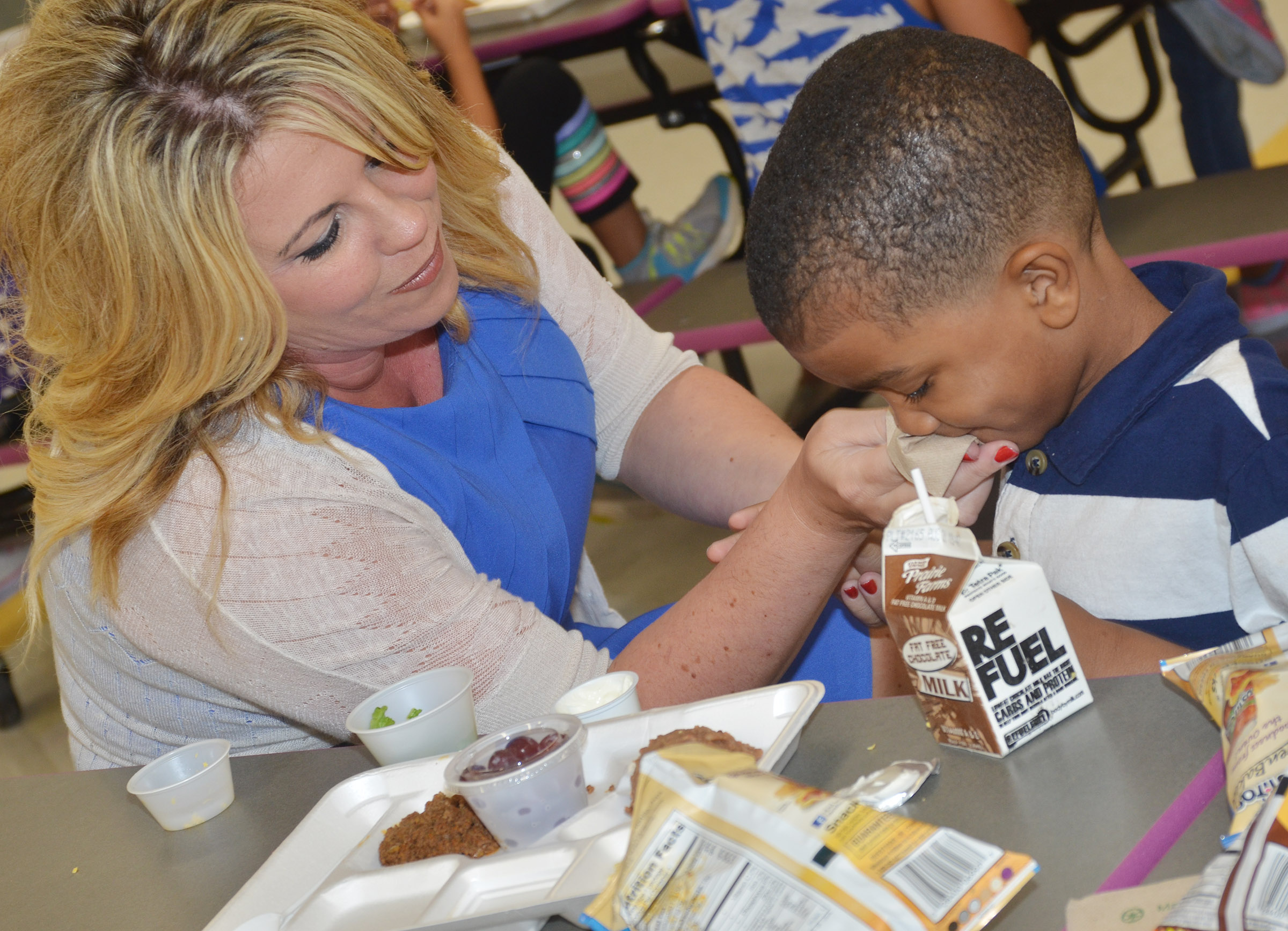 CES Principal Elisha Rhodes helps kindergartener Donavon Bell wipe his mouth.