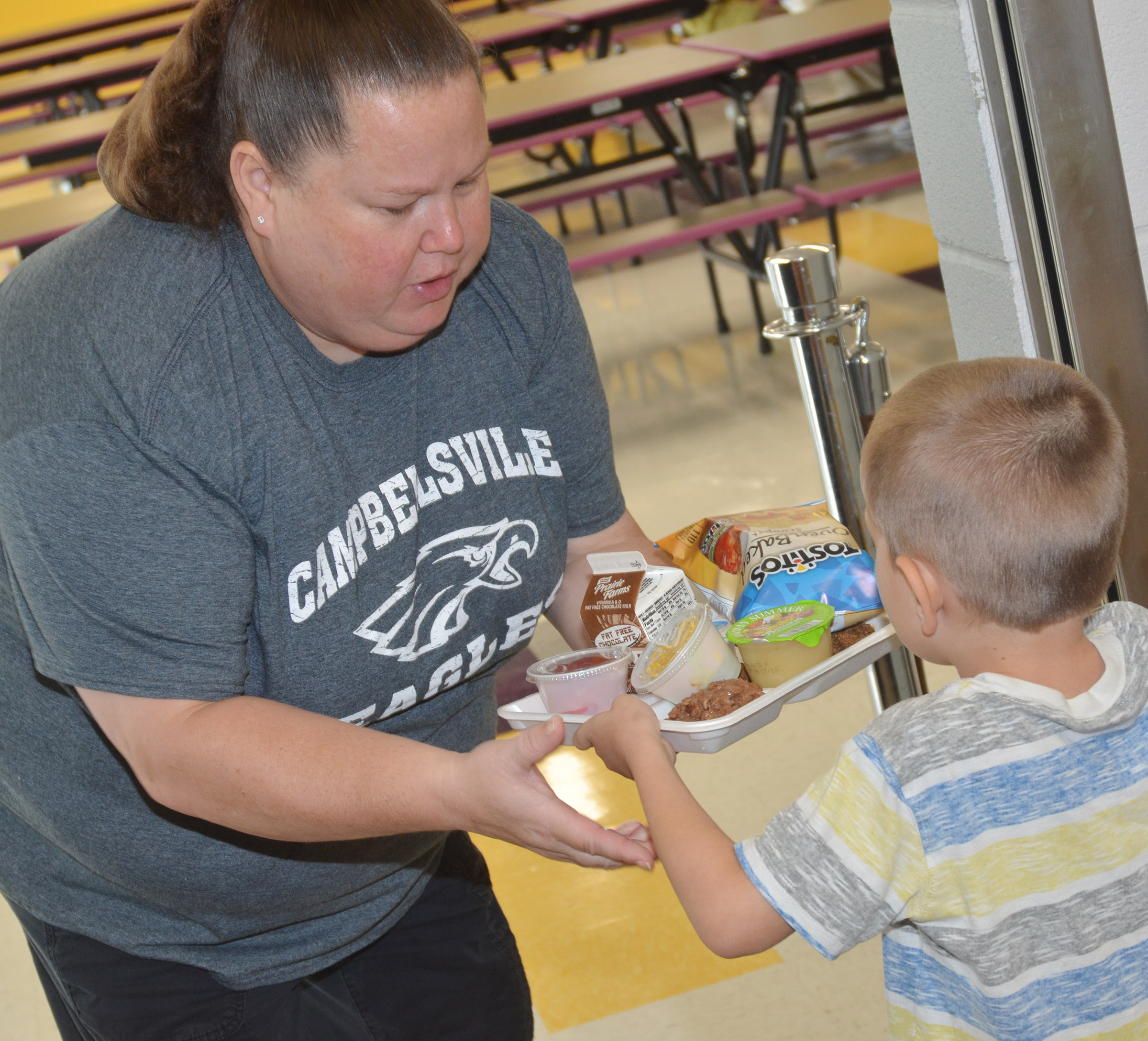 CES cafeteria worker Rebecca Walker helps CES kindergarteners carry their lunch trays.