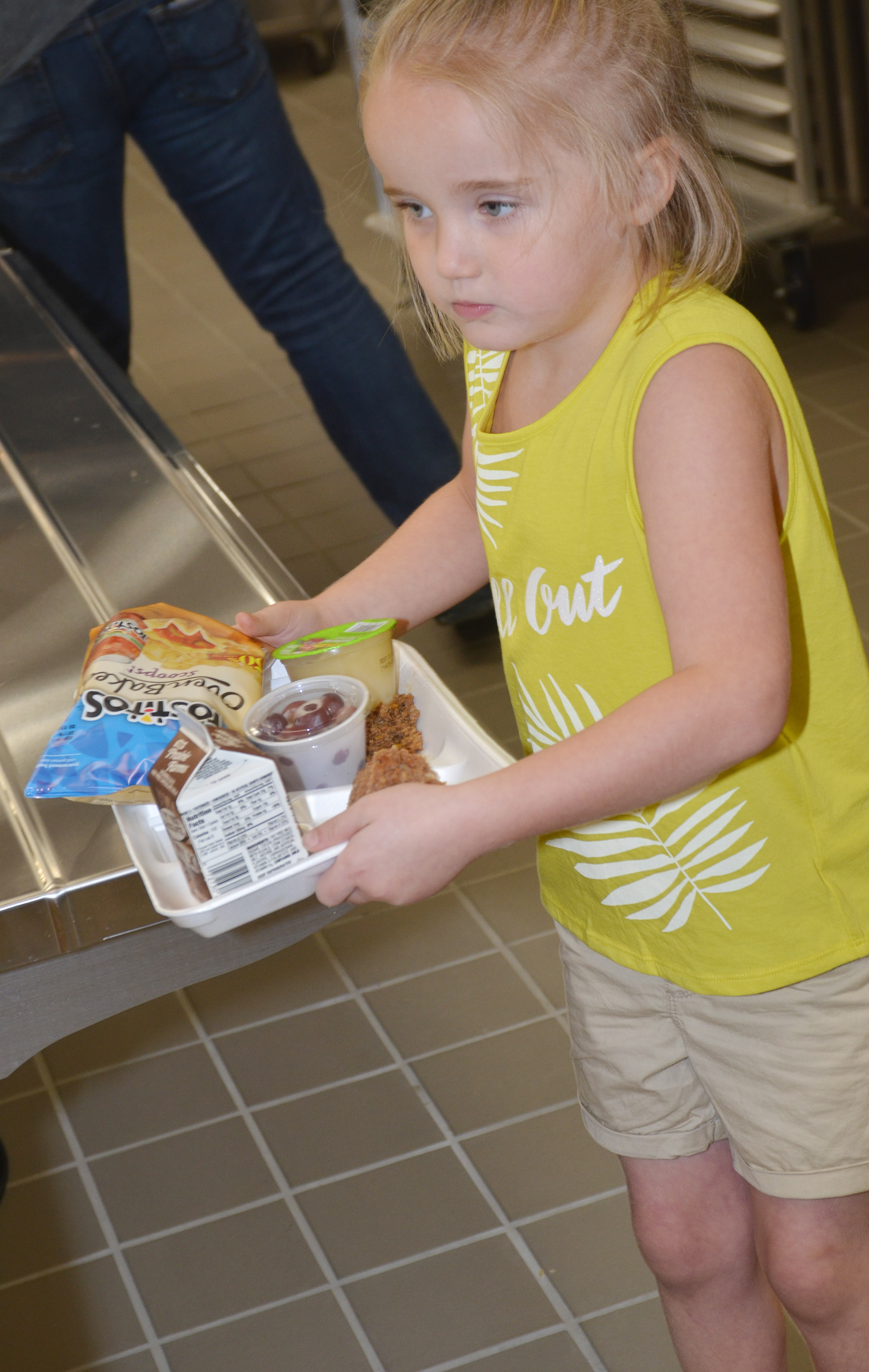 CES kindergartener Trinity Dye carries her lunch tray.