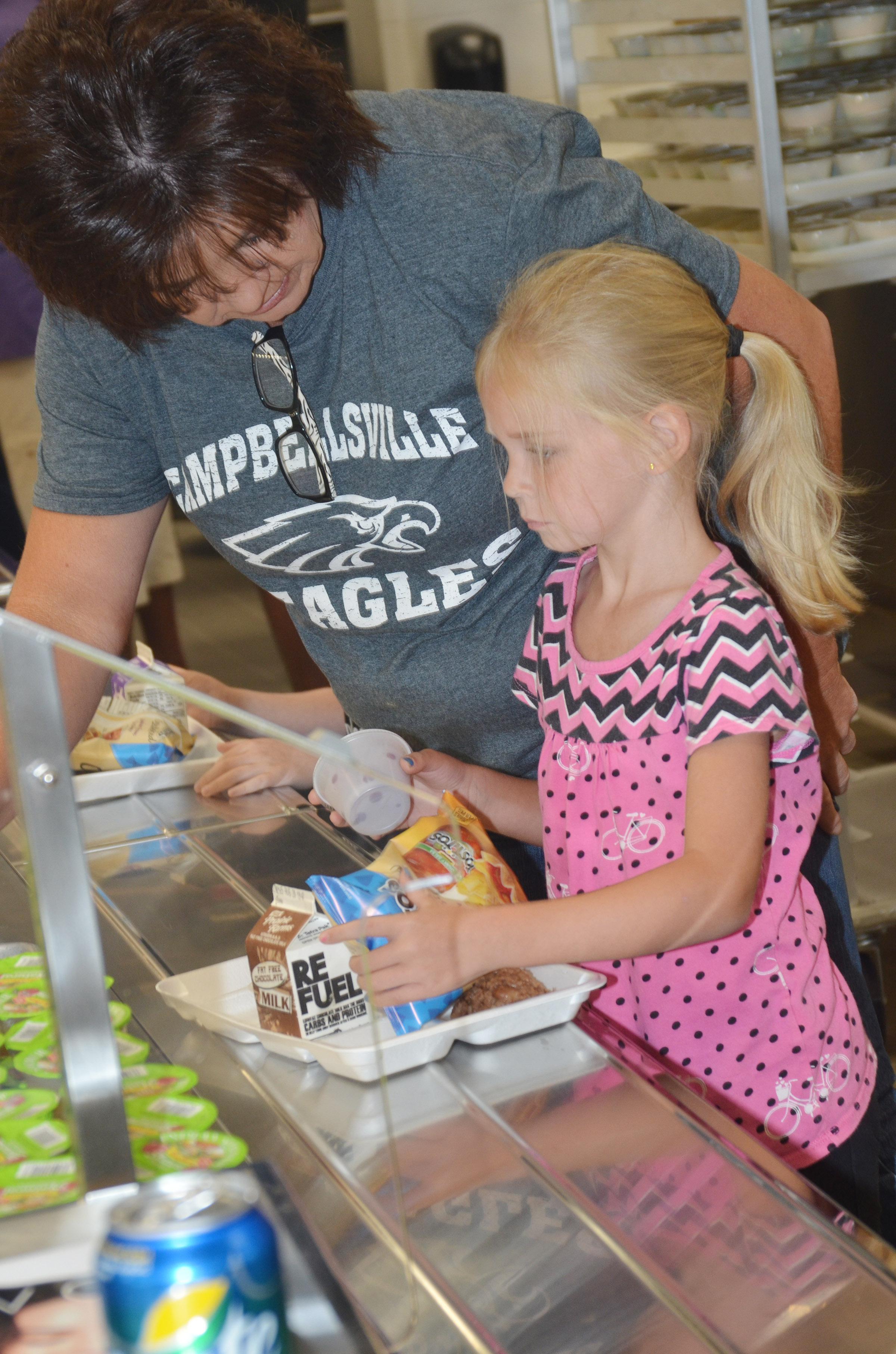 CES cafeteria worker Shelly Wilson helps kindergartener Alinna Bray choose what she wants to eat.