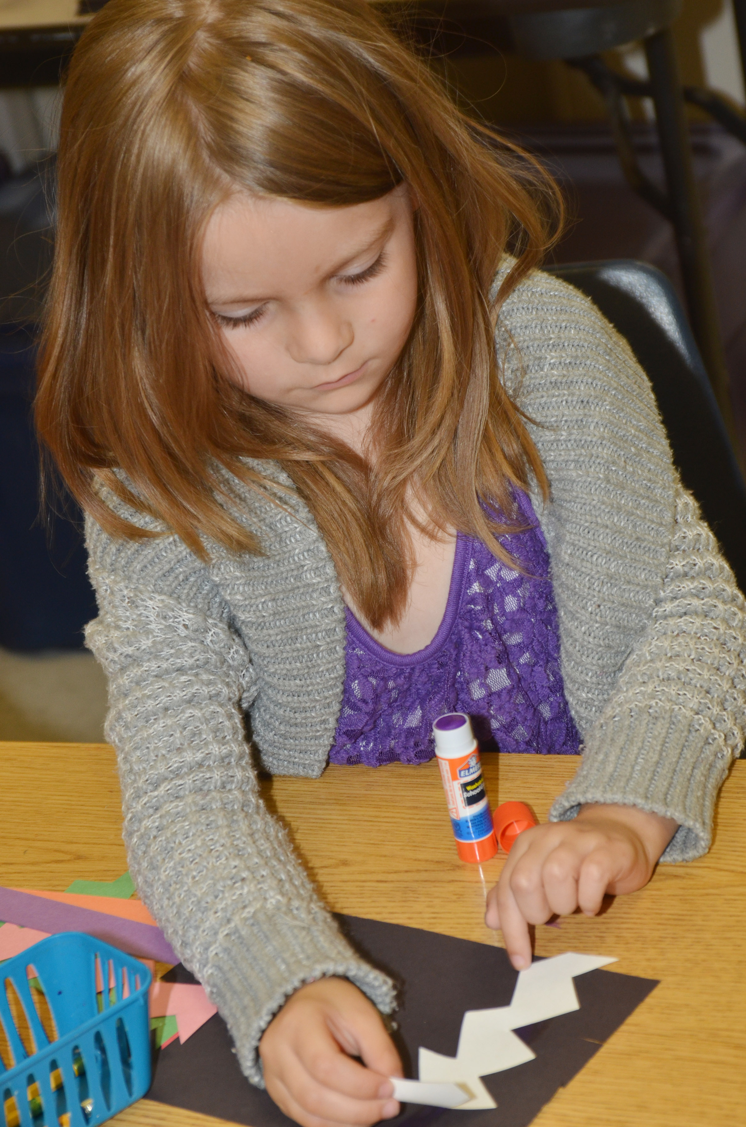 CES kindergartener Daisy Rakes glues a zigzag line on her magic carpet.