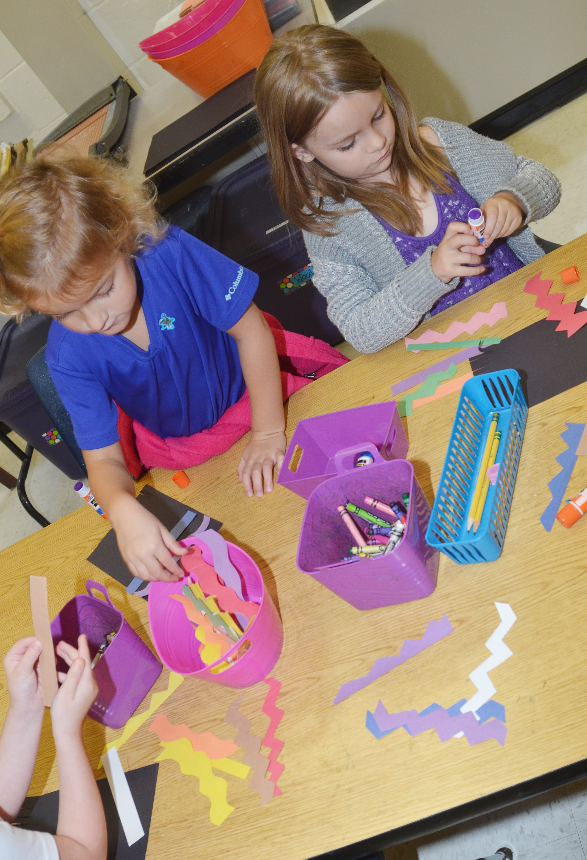 CES kindergarteners Mae Miller, at left, and Daisy Rakes glue lines on their magic carpets.
