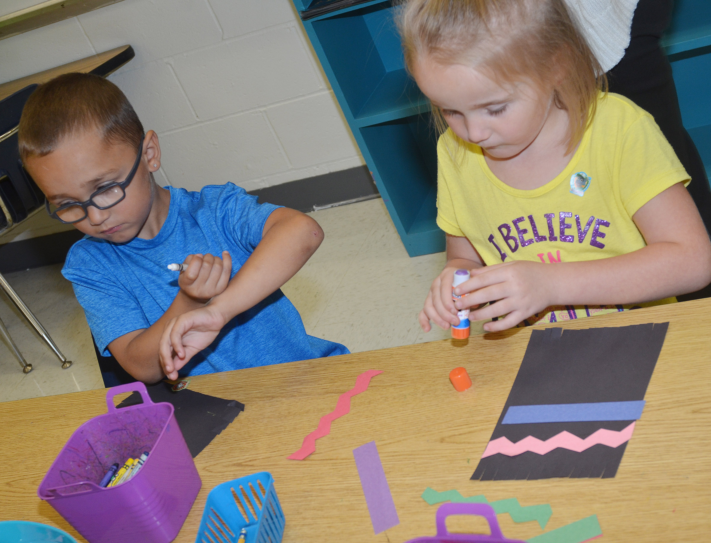 CES kindergarteners Chanler Mann, at left, and Trinity Dye glue lines on their magic carpets.