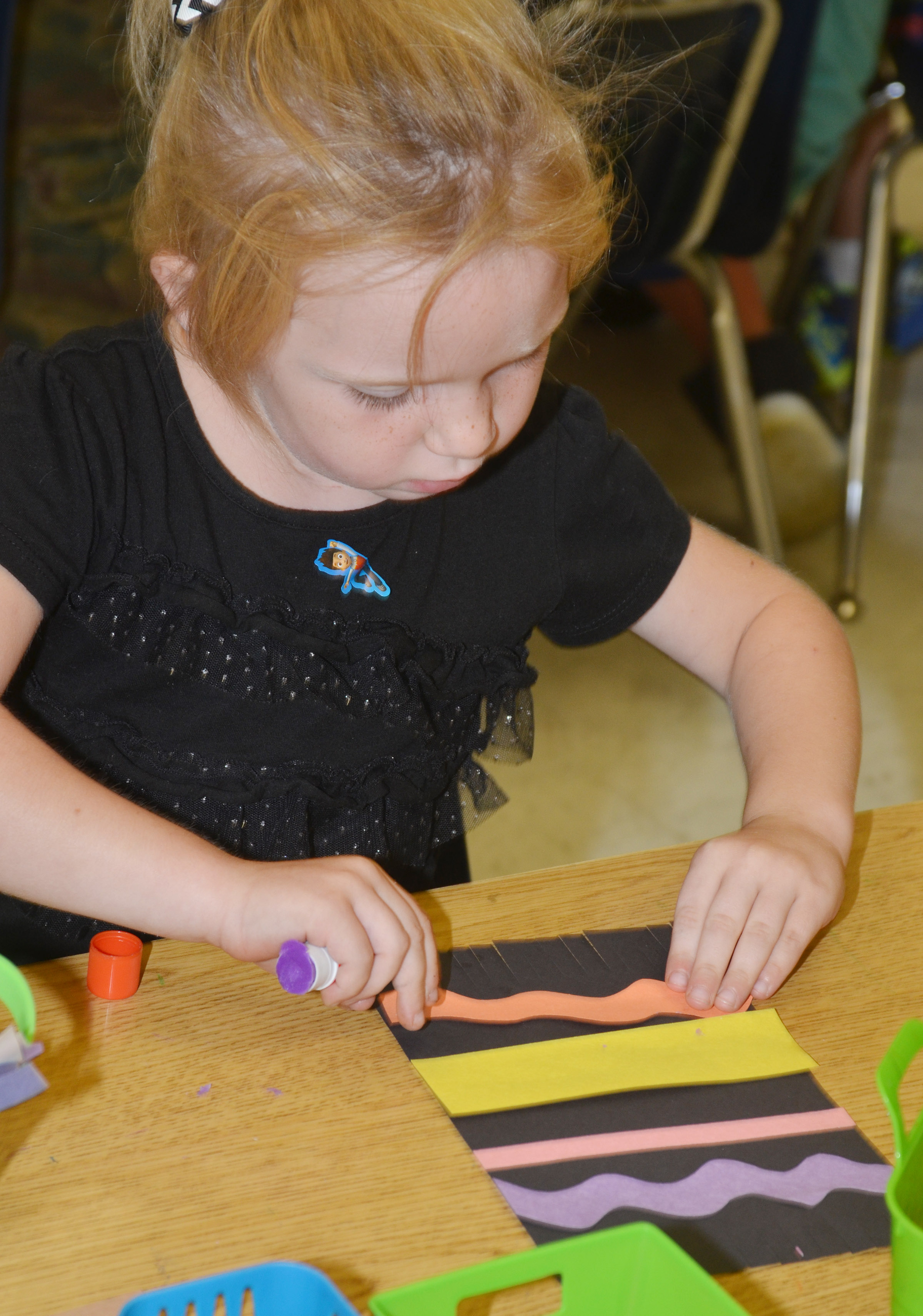 CES kindergartener Macilynn Mann glues a wavy line on her magic carpet.