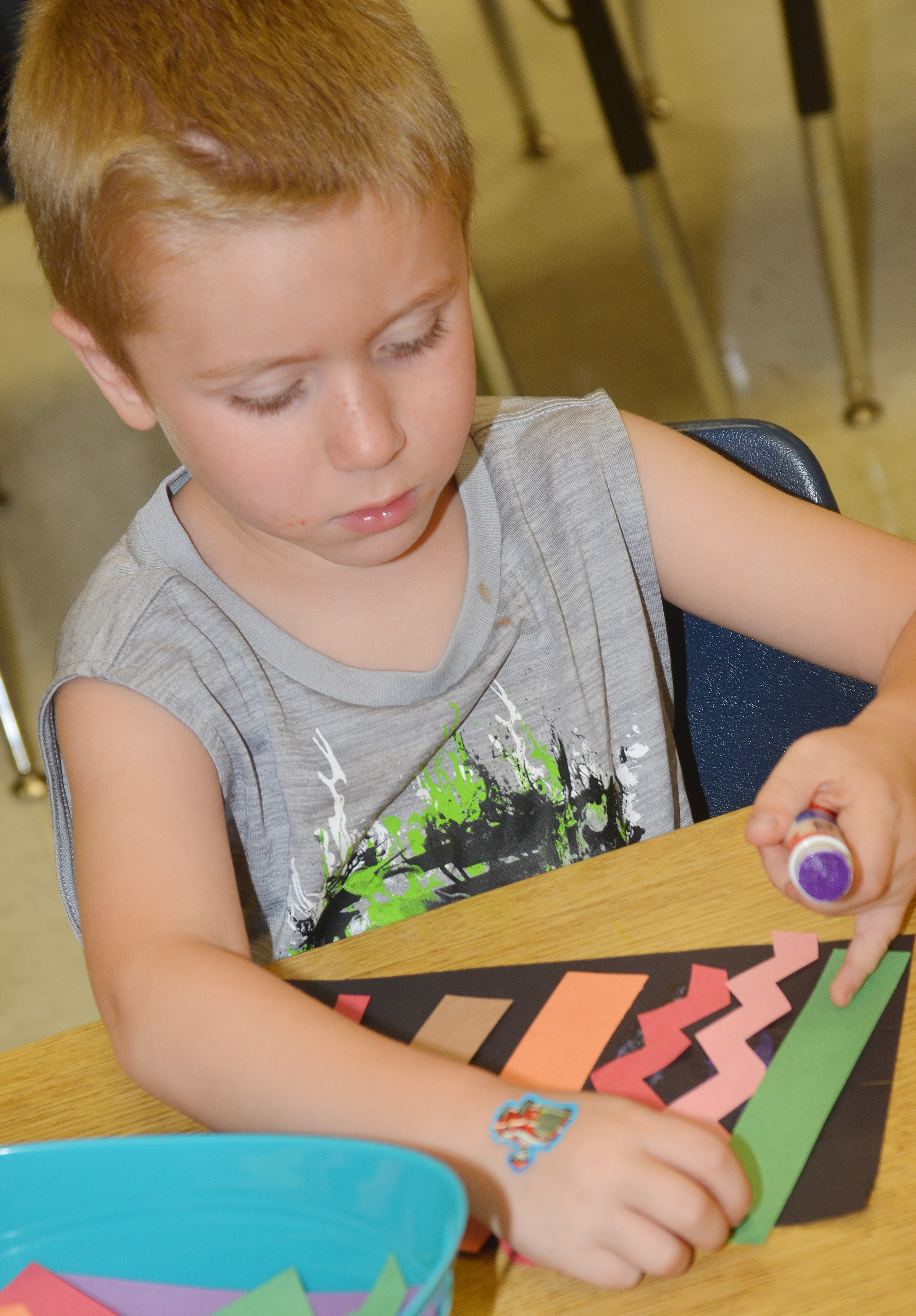 CES kindergartener Alex Newcomb glues a straight line on his magic carpet.