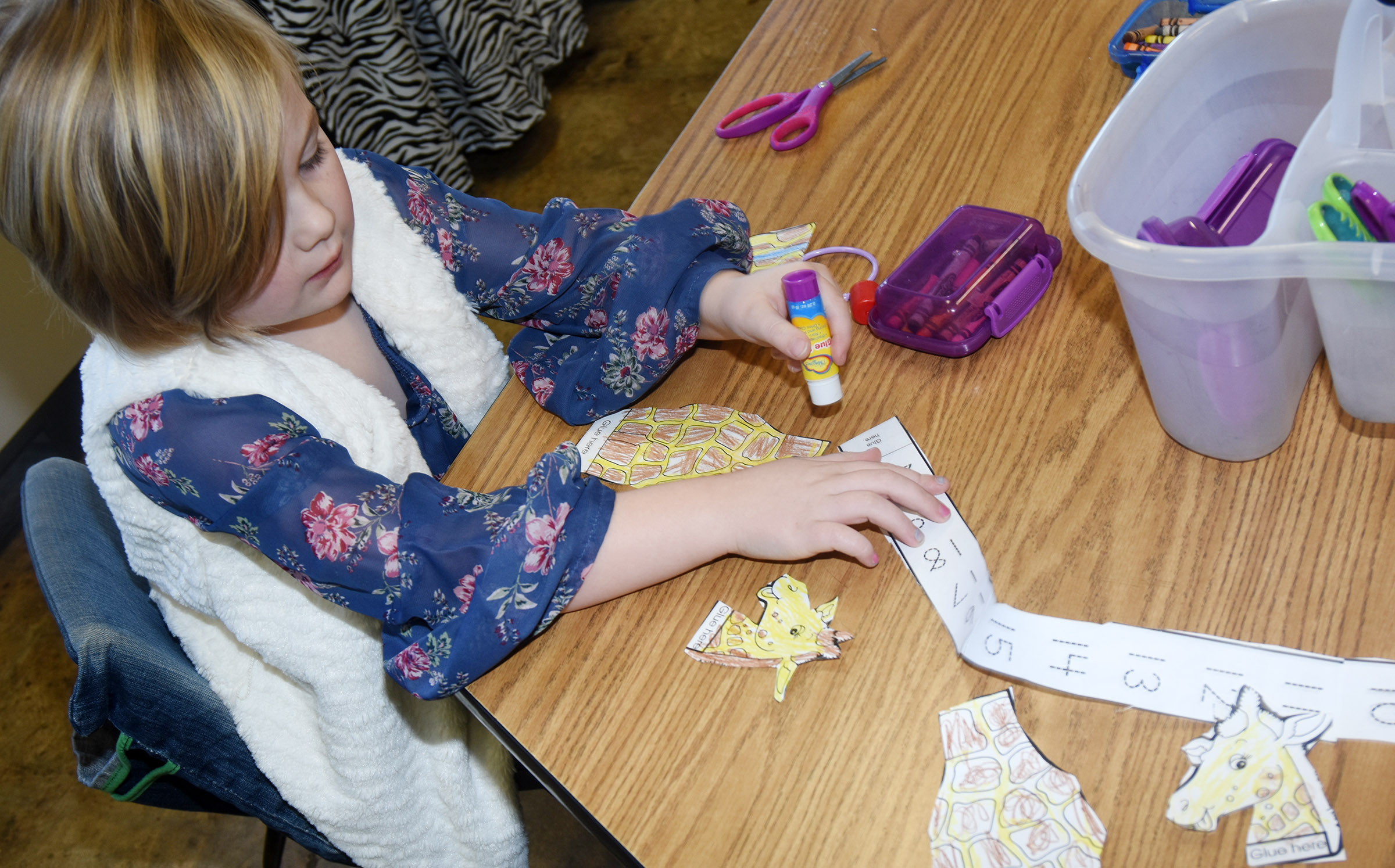 CES kindergartener Zoe Scharbrough glues her giraffe and number line together.