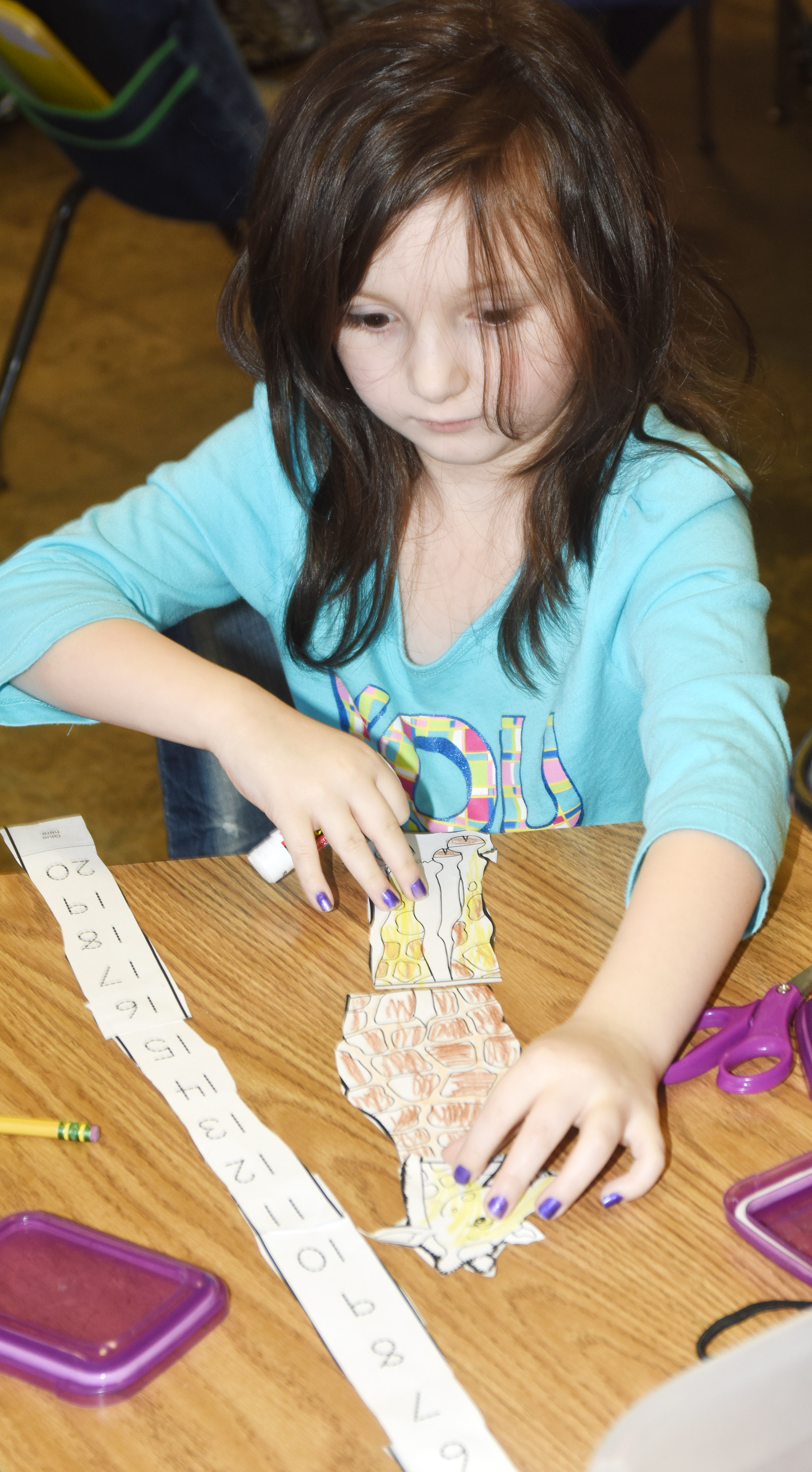 CES kindergartener Abigail Smith glues her giraffe and numbers together.