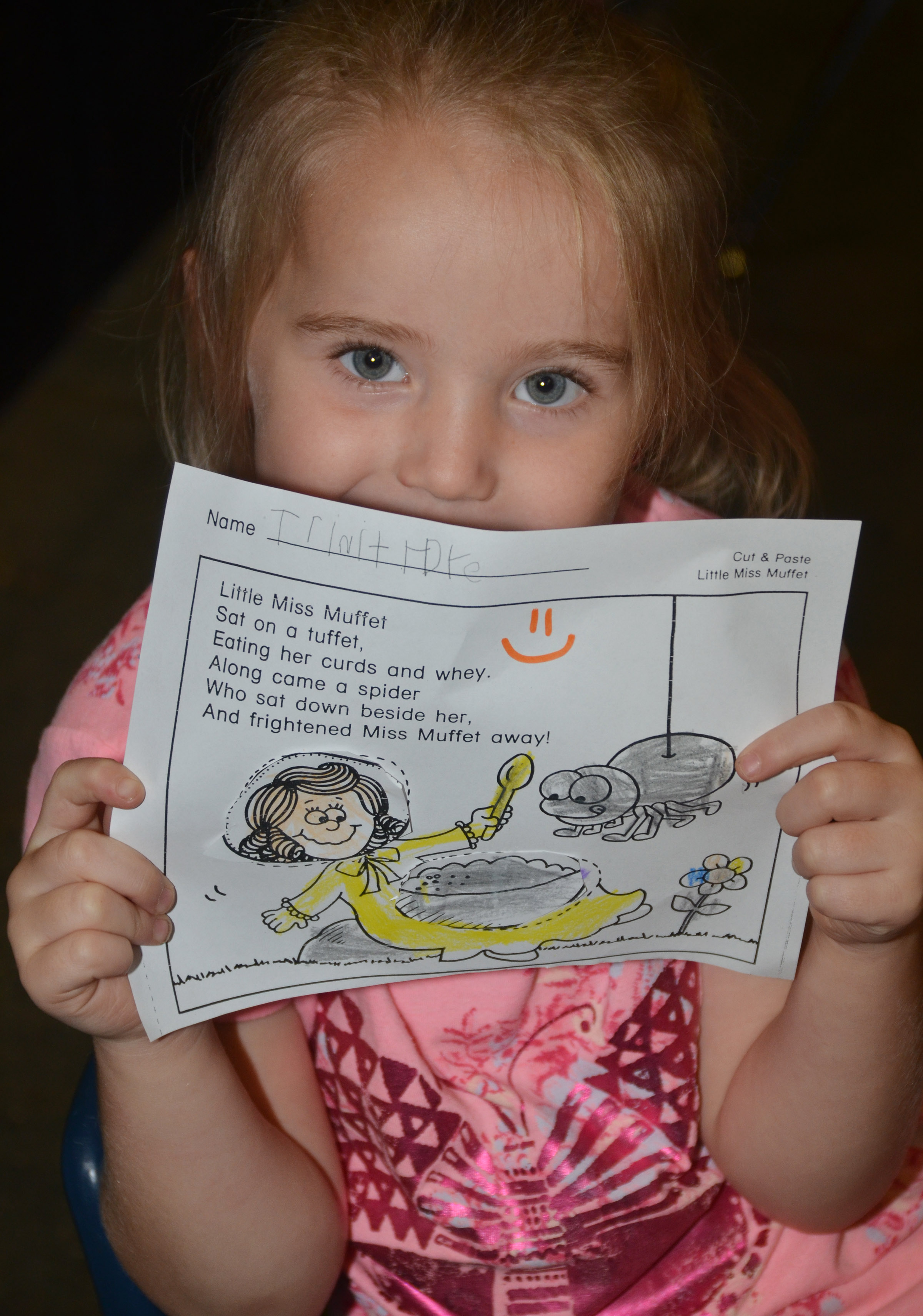 CES kindergartener Trinity Dye holds her finished Little Miss Muffet worksheet.