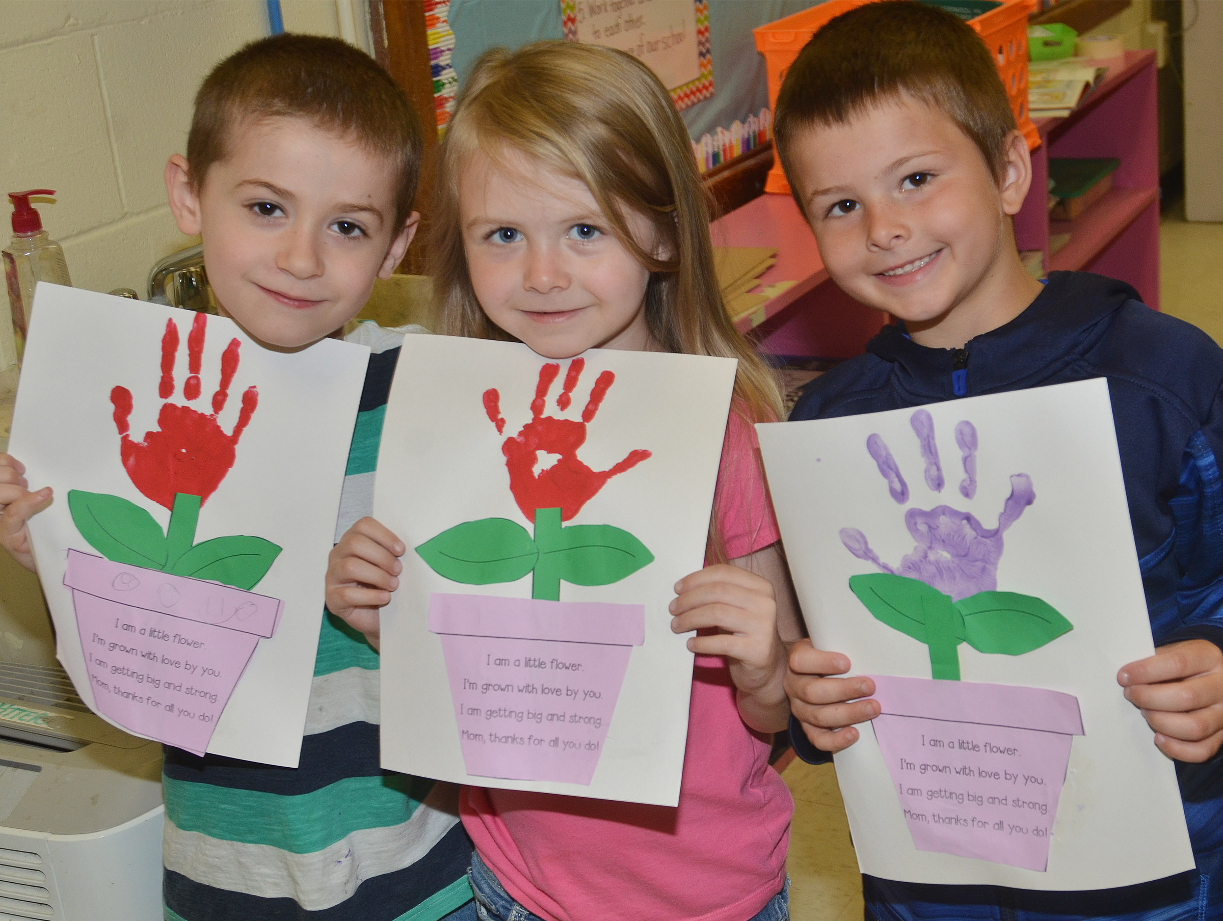 From left, CES kindergarteners Greyson Trulock, Jewell Brewster and Zain Mullins hold their Mother's Day flowers.