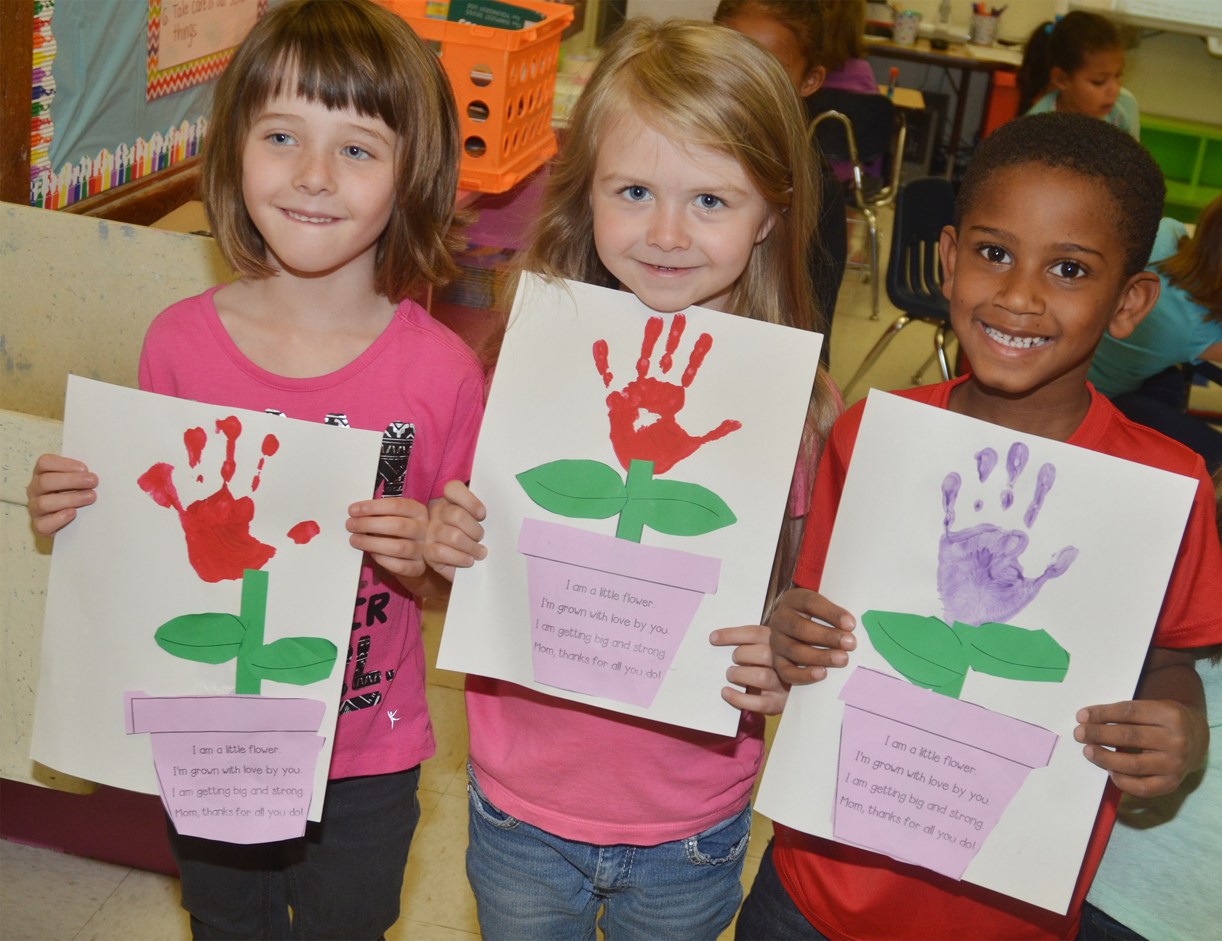 CES kindergarteners, from left, Serenity Bell, Jewell Brewster and Kasen Smith hold their Mother's Day flowers.