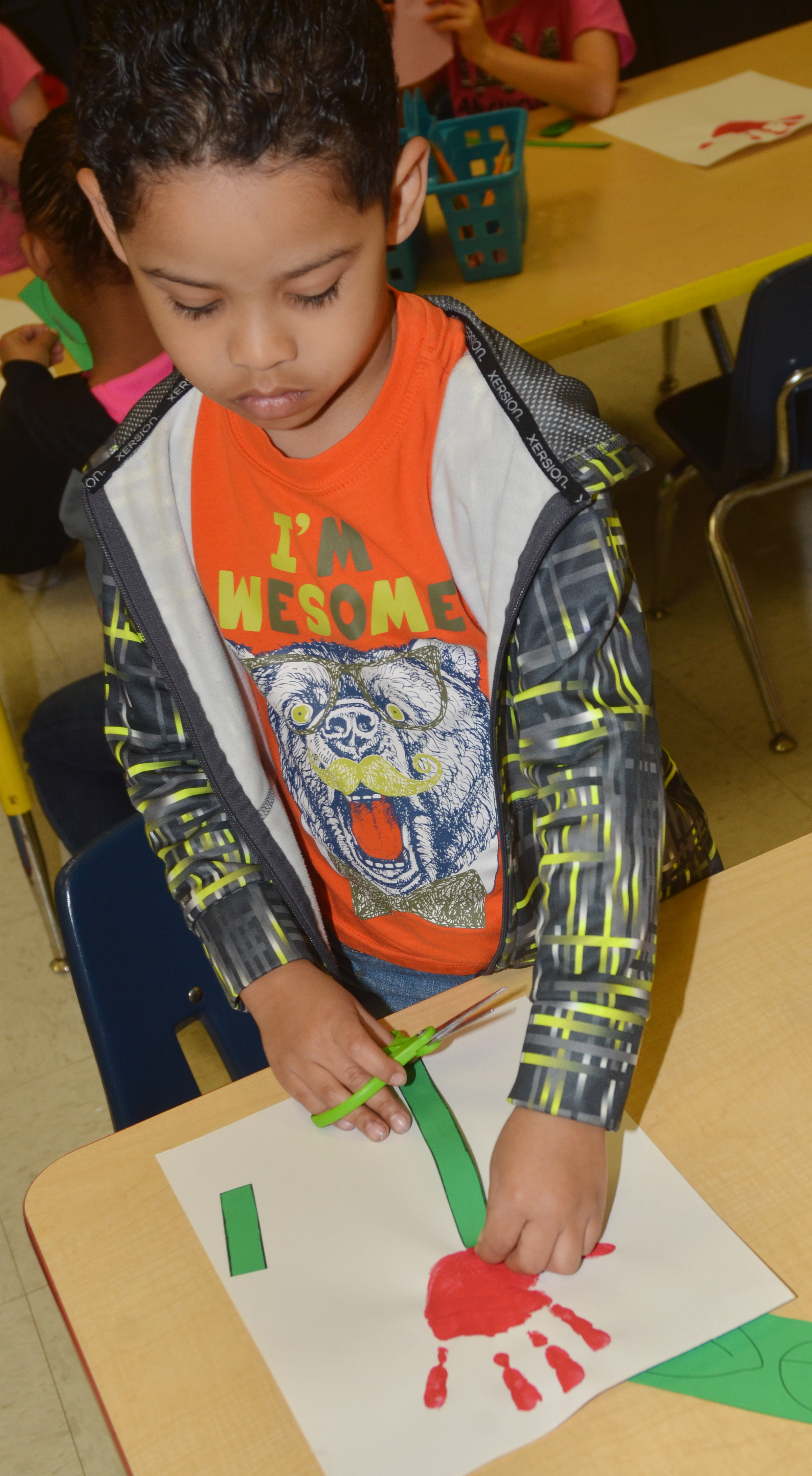 CES kindergartener Demarcus Noyola makes his Mother's Day flower.
