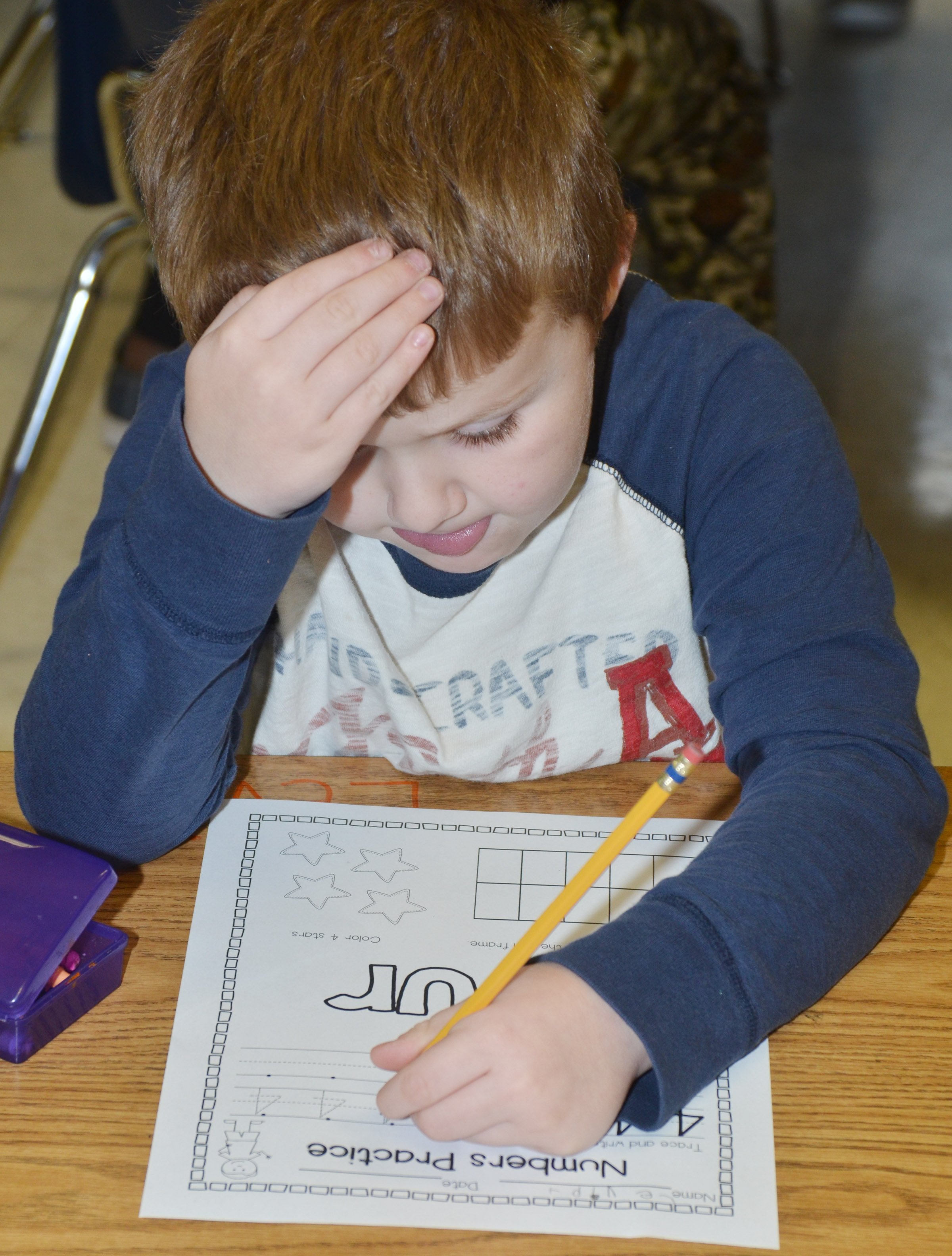 CES kindergartener Levi Dye concentrates as he writes the number four.