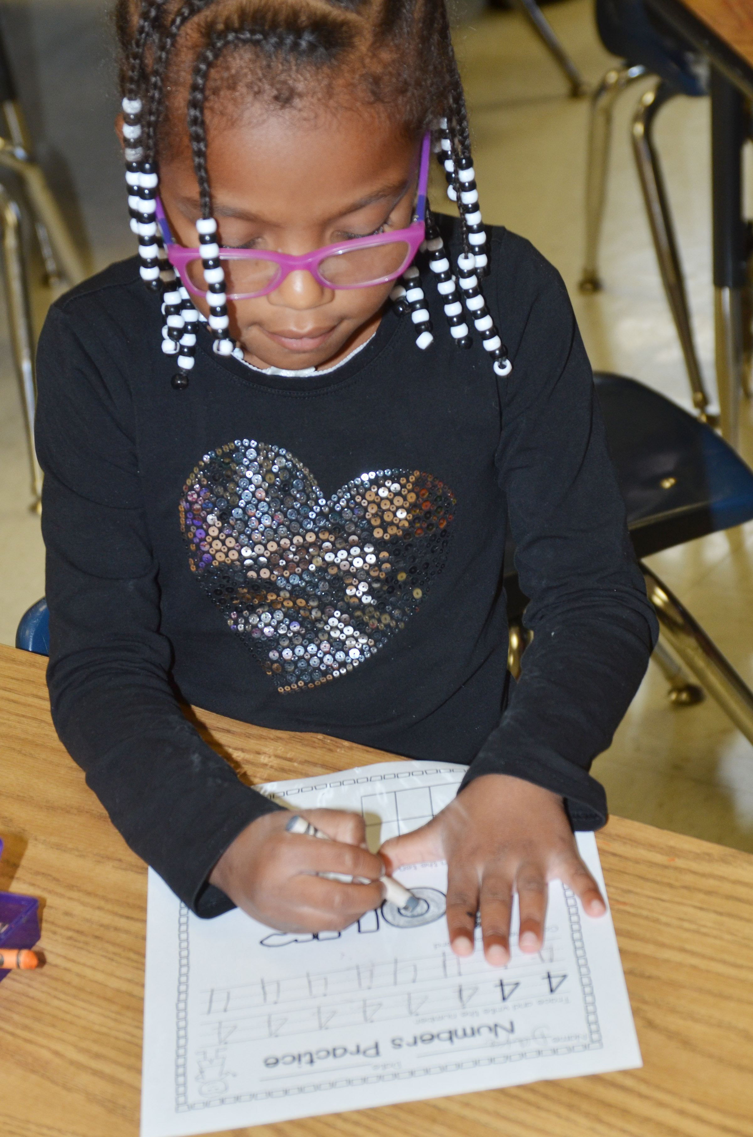 "CES kindergartener Daya Griffin colors the word ""four."""