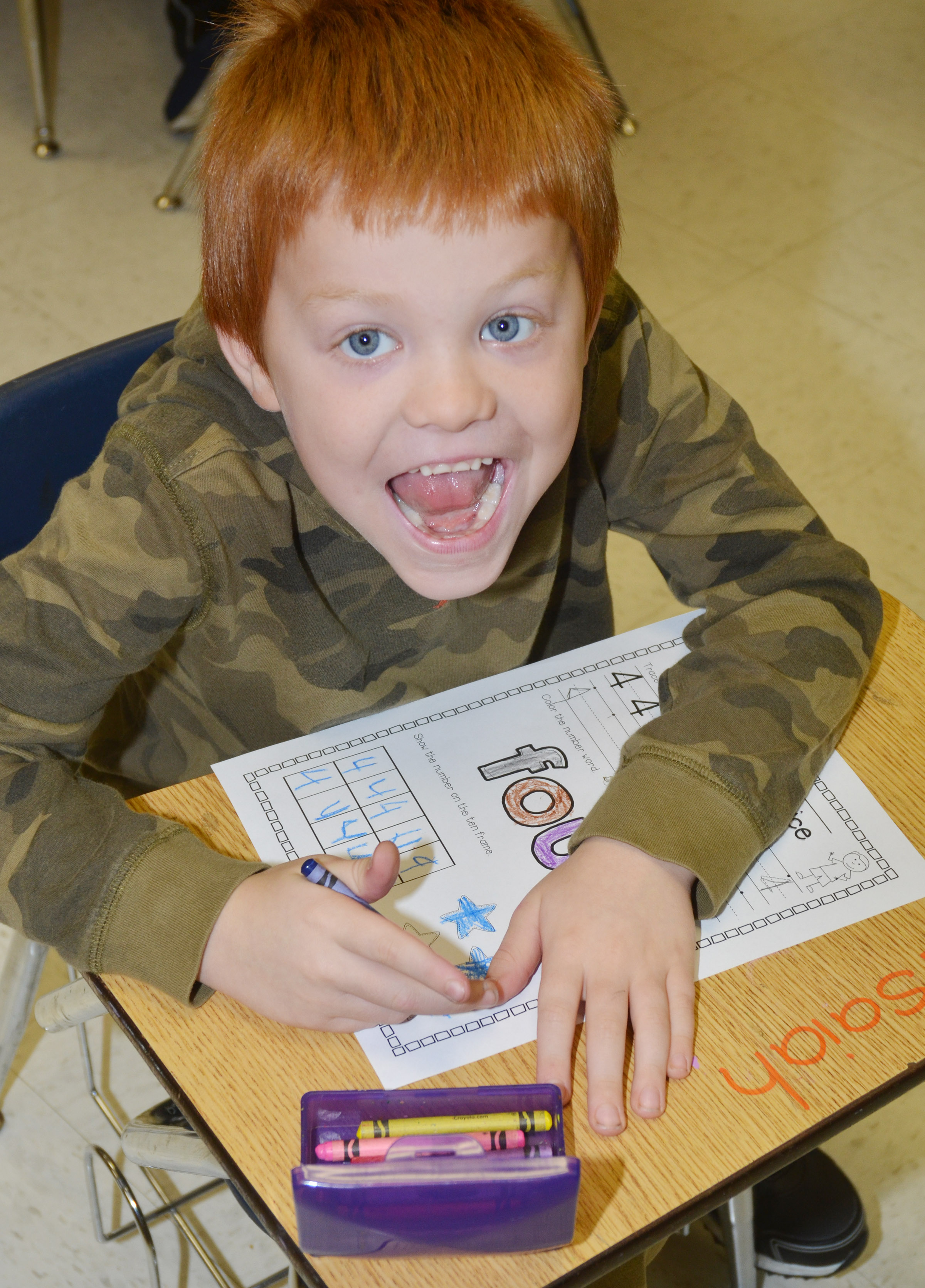 "CES kindergartener Cambrien Couch smiles as he works on his ""four"" worksheet."
