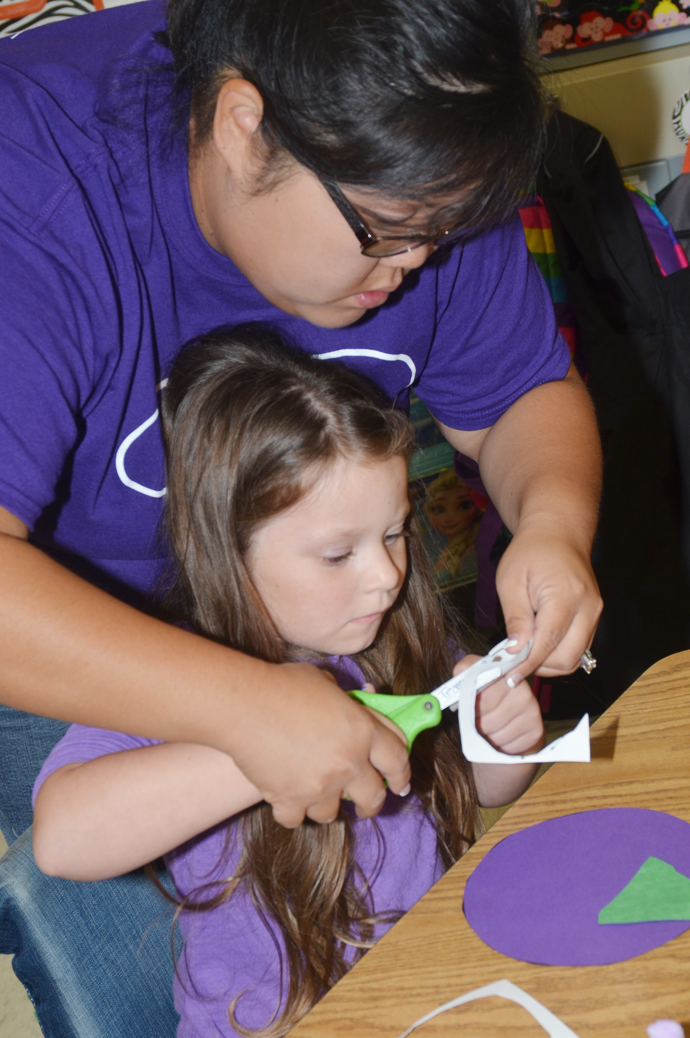 CES kindergarten assistant Brittany Johnson helps Gracie McKenzie cut out an eye for her purple people eater.
